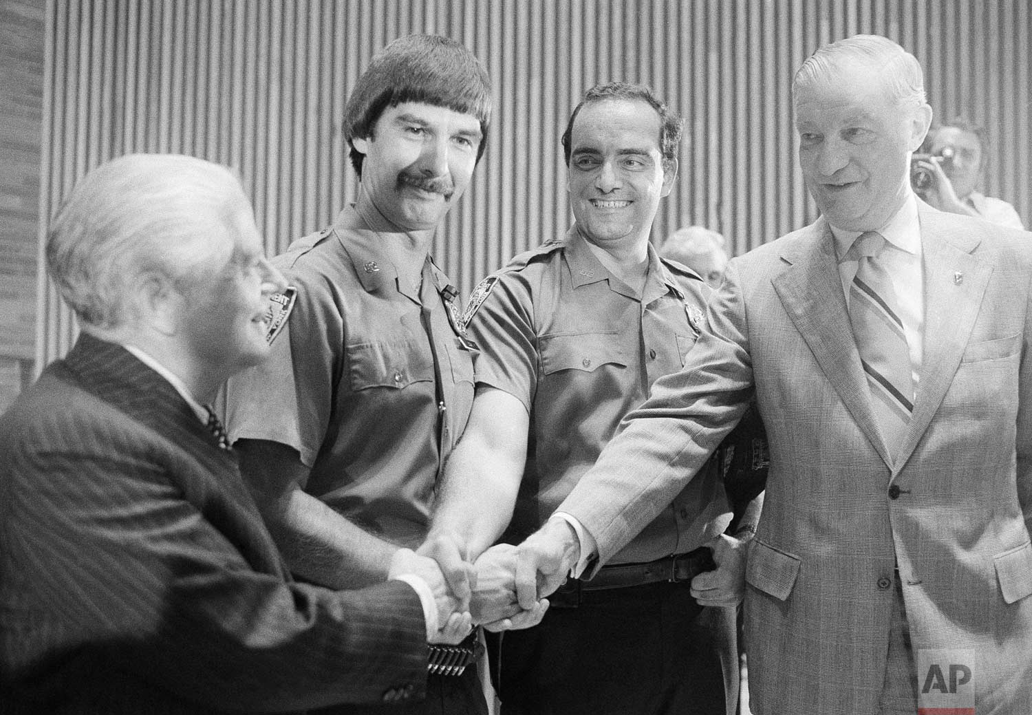 "New York Mayor Abraham Beame, left, and police commissioner Michael Codd, right, shake hands at Police Headquarters, Thursday, Aug. 11, 1977 with officers Jeffrey Logan, second from left, and Michael Cataneo. A parking ticket issued by the two officers to a car at the site of the "".44 Caliber Killer's"" last shooting led police on Wednesday night to the home of a suspect police believed to be the ""Son of Sam"" gunman. (AP Photo/Dave Pickoff)"