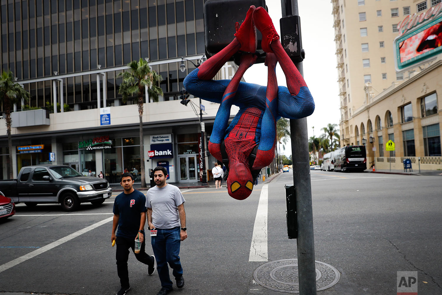 In this Thursday, May 25, 2017 photo, Rashad Rouse, 27, whose dream is getting his star on the Hollywood Walk of Fame, hangs upside down from a traffic signal pole in a Spider-Man costume to get attention from tourists on Hollywood Boulevard, in Los Angeles. Rouse is a musician and sometimes works as an Uber driver when he is not working on the boulevard. (AP Photo/Jae C. Hong)
