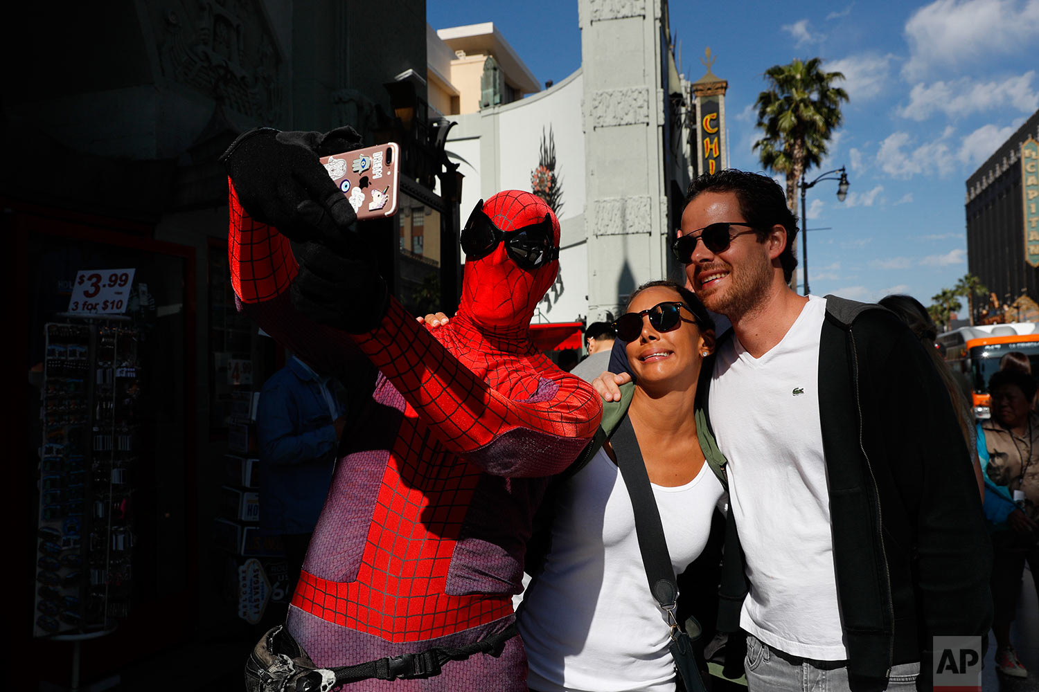"In this Wednesday, May 24, 2017 photo, superhero impersonator and actor Dan Inigo, left, uses a tourist's smartphone to take a selfie on Hollywood Boulevard in Los Angeles. ""It's a place of diversity, it's a place of drama, it's a place of illusion … a place of broken dreams,"" says the 25-year-old actor who prowls the boulevard dressed as Spider-Man. Although he barely scrapes by, Inigo says it's still a great gig for a struggling actor who needs to keep a schedule open for auditions. (AP Photo/Jae C. Hong)"