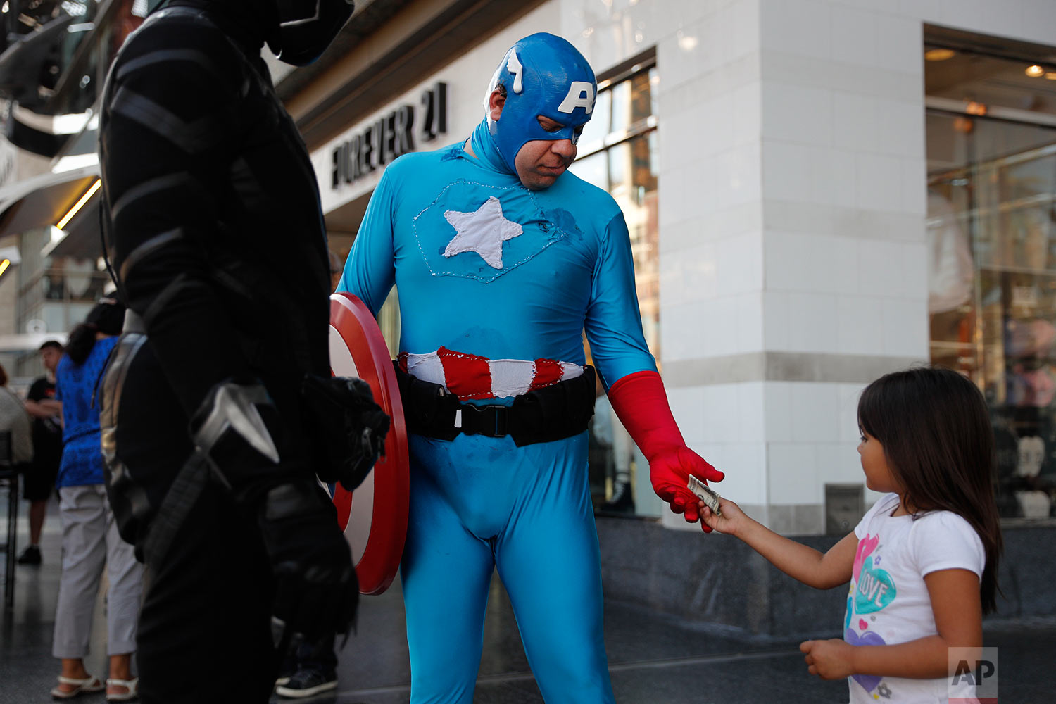 In this Monday, May 22, 2017 photo, a young tourist tips Justin Harrison, wearing a homemade Captain America costume, and Harrison's roommate, Reginald Jackson in a Black Panther costume after taking pictures with them on Hollywood Boulevard in Los Angeles. While the Hollywood we see in film is a place of glamour and beautiful celebrities, the cast of superheroes filling Hollywood Boulevard is frequently anything but. Many are people struggling to make a buck as they pursue their dream of stardom. (AP Photo/Jae C. Hong)