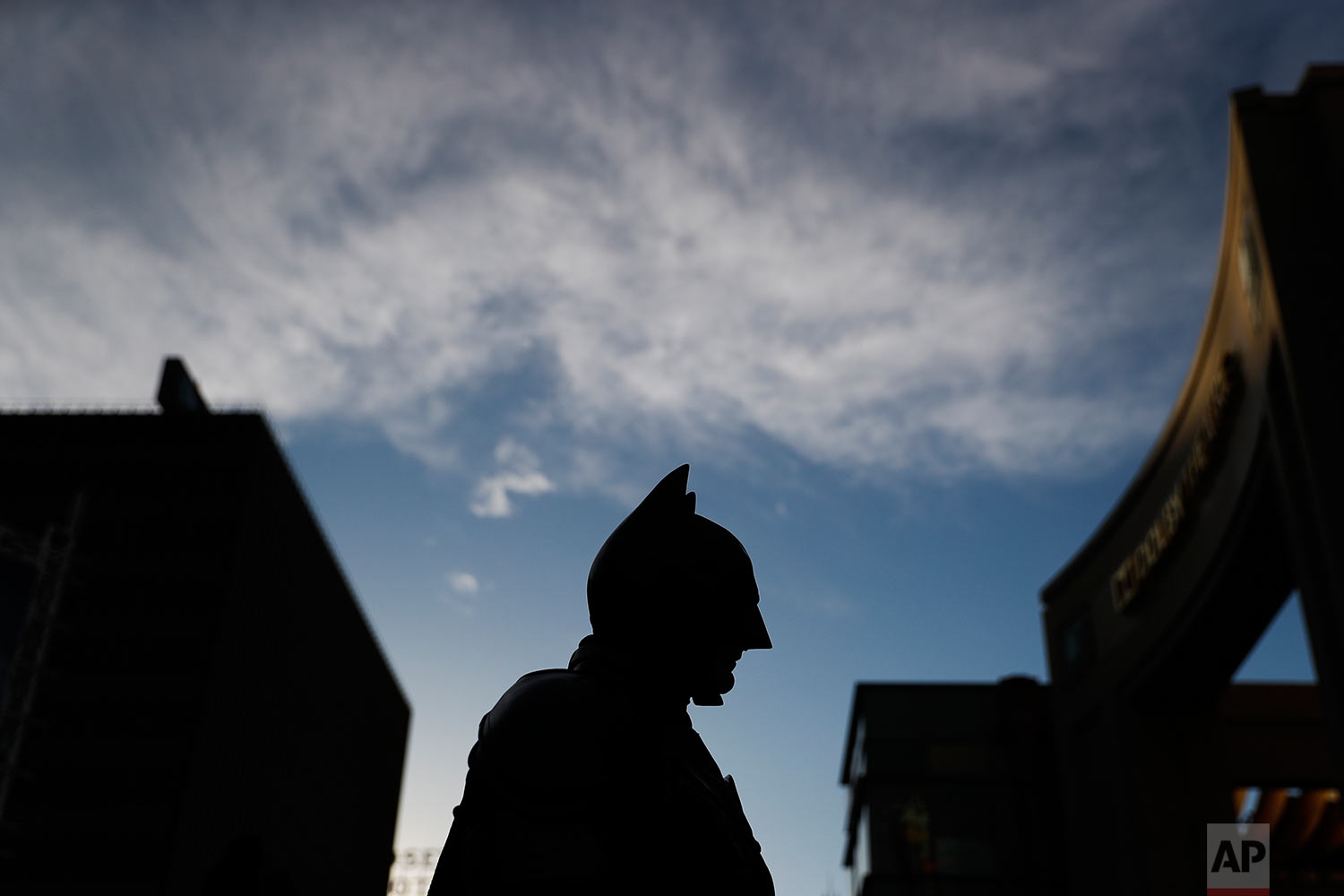 "In this Thursday, March 2, 2017 photo, Batman impersonator Matthias Balke is silhouetted while standing on Hollywood Boulevard near the Dolby Theatre in Los Angeles. Wearing his $3,000 Batman costume, Balke said he doesn't grab tourists or crack a joke to get their attention. Instead, he waits for them to come to him. ""My way of soliciting is the quality of my costume,"" he said. ""People see it, they come to me to ask me for a picture. I'd never walk up to anybody."" (AP Photo/Jae C. Hong)"