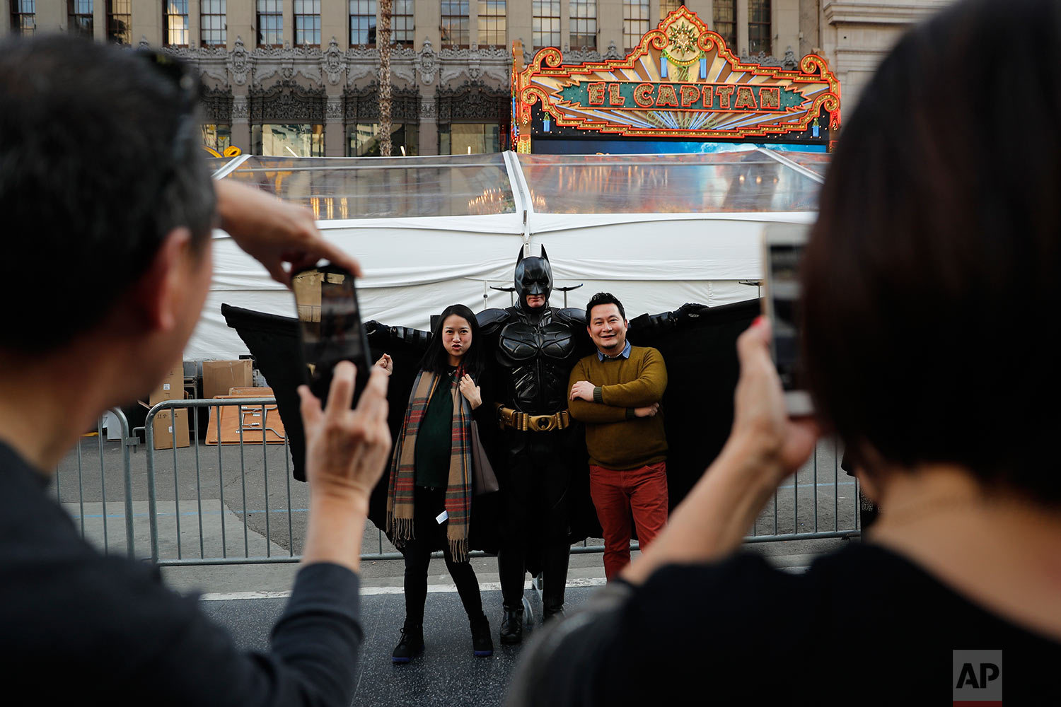 "In this Thursday, March 2, 2017 photo, superhero impersonator Matthias Balke poses with tourists on Hollywood Boulevard near the Dolby Theatre in Los Angeles. The screenwriter-producer-actor, who put $3,000 into his elaborate Batman ensemble, said he doesn't grab tourists or crack a joke to get their attention. Instead, he waits for them to come to him. ""My way of soliciting is the quality of my costume,"" he said. ""People see it, they come to me to ask me for a picture. I'd never walk up to anybody."" (AP Photo/Jae C. Hong)"