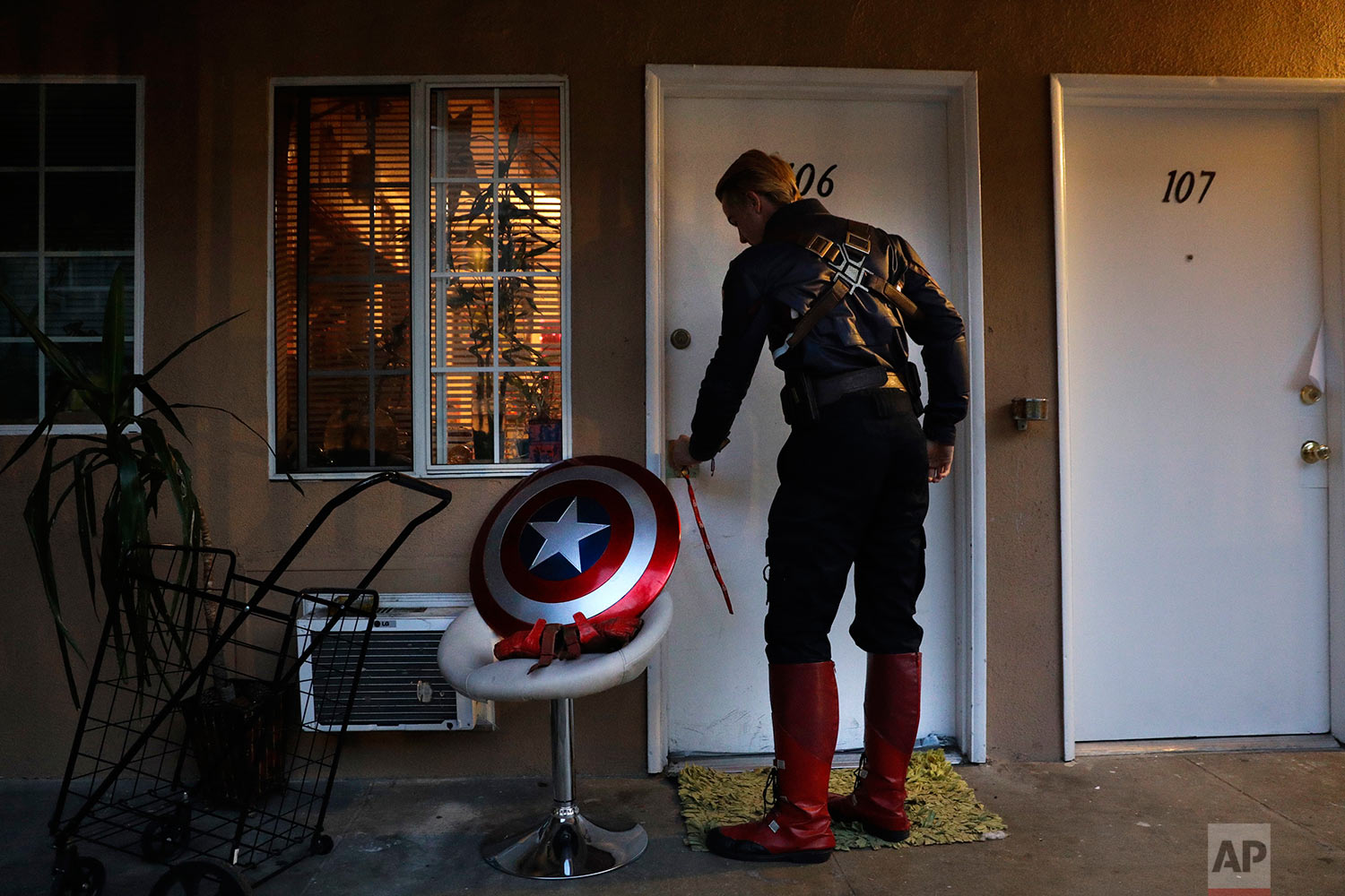 "In this Monday, May 8, 2017 photo, Captain America impersonator Henry Hodge, a cinematographer from England who lives a stone's throw away from Hollywood's Dolby Theatre, opens his apartment door in Los Angeles. ""The boulevard is the only thing that gives me the freedom to do what I really want to do,"" said Hodge. ""I never have to miss a film meeting. I'm always available to shoot."" (AP Photo/Jae C. Hong)"