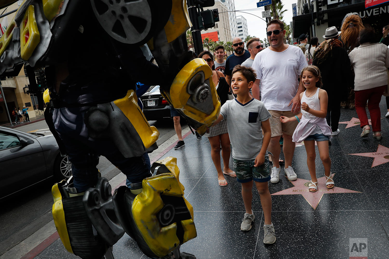 In this Friday, May 26, 2017 photo, Ramiro Rodriguez in a Bumblebee costume, a character from the Transformers movie series, shakes hands with young tourists on Hollywood Boulevard, in Los Angeles. The 39-year-old former restaurant worker from Guadalajara, Mexico, changed his career after watching a film on Hollywood characters. Rodriguez and his brother invested all their savings in the costume. Even on bad days, Rodriguez said they still make enough to buy dinner. (AP Photo/Jae C. Hong)