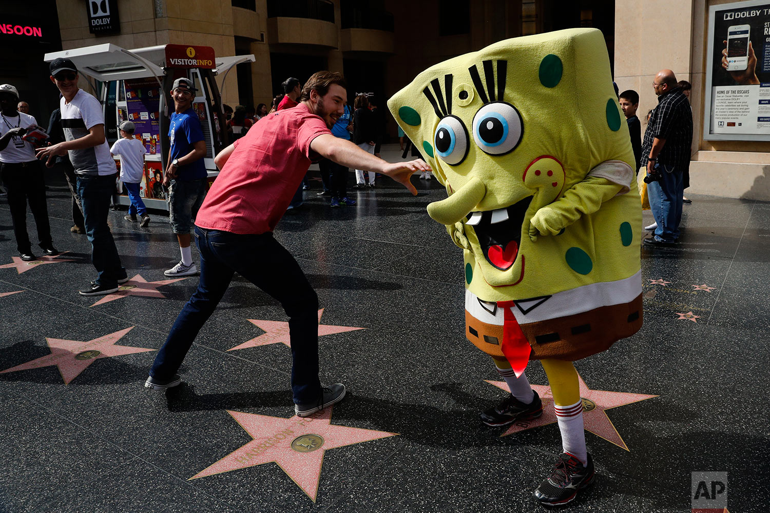"In this Monday, April 17, 2017 photo, Belnarr Golden, wearing a SpongeBob SquarePants costume, dodges a tourist trying to pull the nose of his costume on Hollywood Boulevard, in Los Angeles. Longtime street performers say the business used to be more lucrative, until the boulevard became overpopulated with costumed characters.  ""I crack jokes on them. That's my trick. I make them laugh,"" said Golden. ""If I stand still, I'm not getting paid."" (AP Photo/Jae C. Hong)"