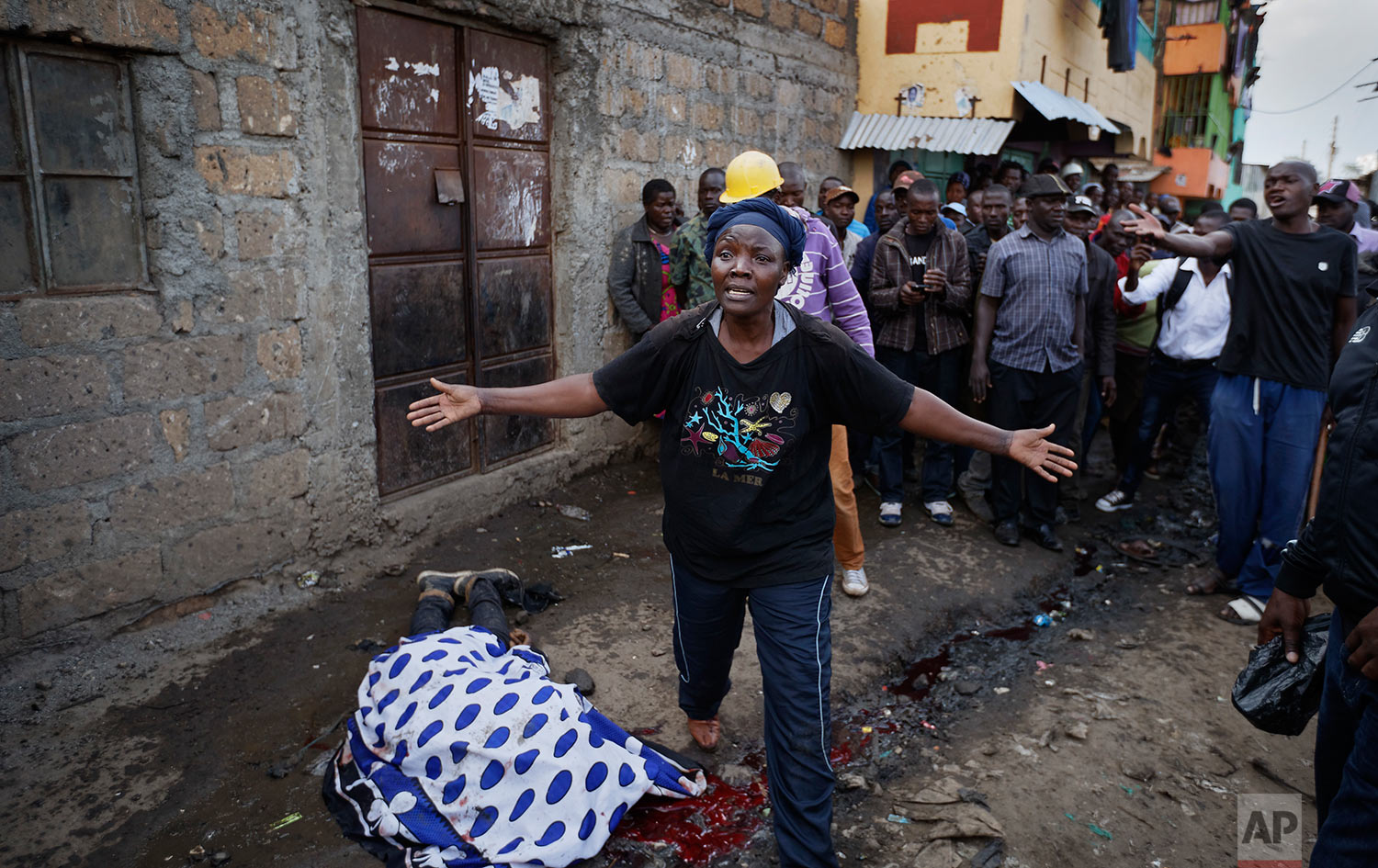 A woman wails in front of the covered body of a man who had been shot in the head and who the crowd claimed had been shot by police, as the angry crowd shouts towards the police, in the Mathare slum of Nairobi, Kenya, Wednesday, Aug. 9, 2017. Kenya's election took an ominous turn on Wednesday as violent protests erupted in the capital. (AP Photo/Ben Curtis)