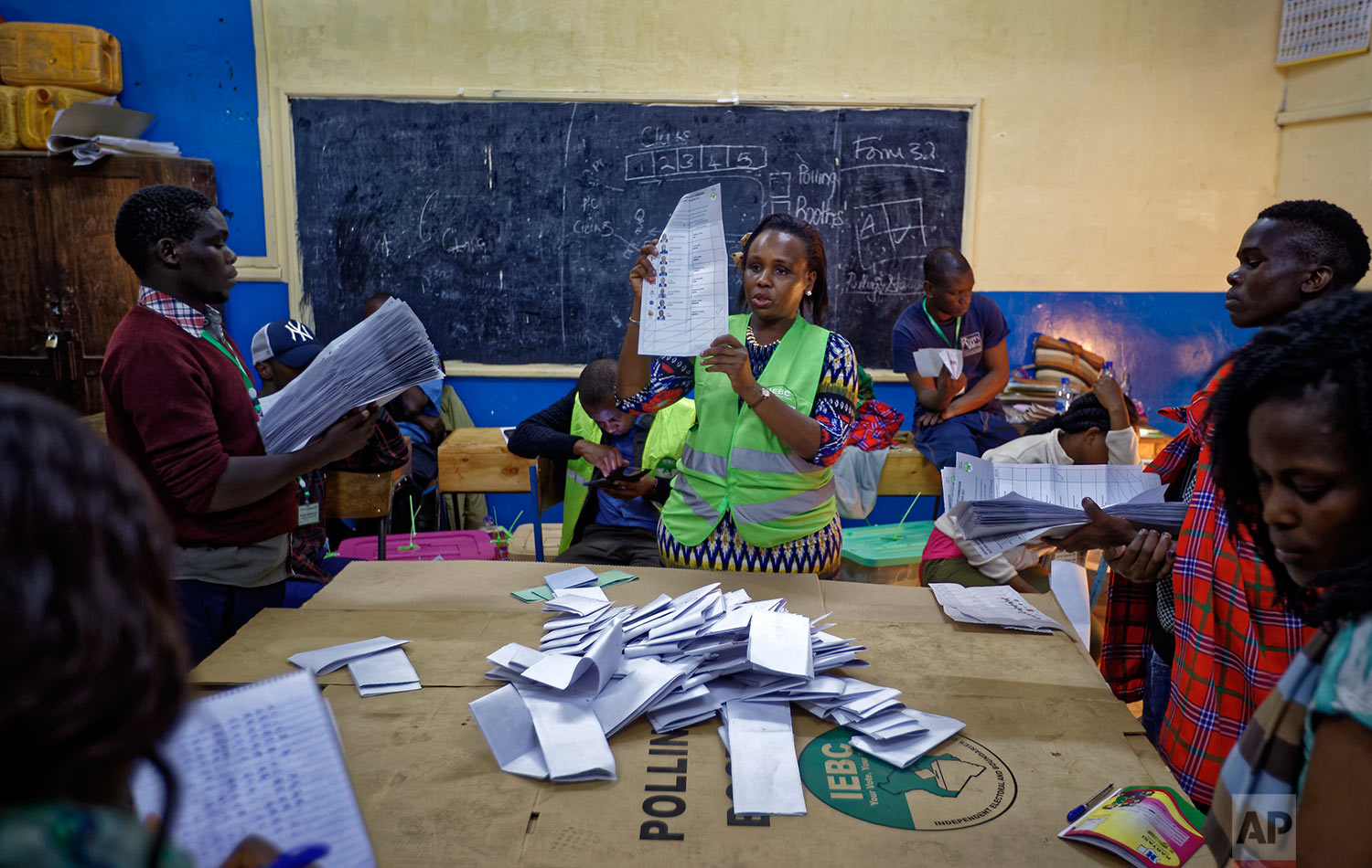 An electoral counting officer, center, counts votes while others hold the piles of ballots counted for each candidate, at a polling station in Nairobi, Kenya, Tuesday, Aug. 8, 2017. Kenyans are going to the polls to vote in a general election after a tightly-fought presidential race between incumbent President Uhuru Kenyatta and main opposition leader Raila Odinga. (AP Photo/Ben Curtis)