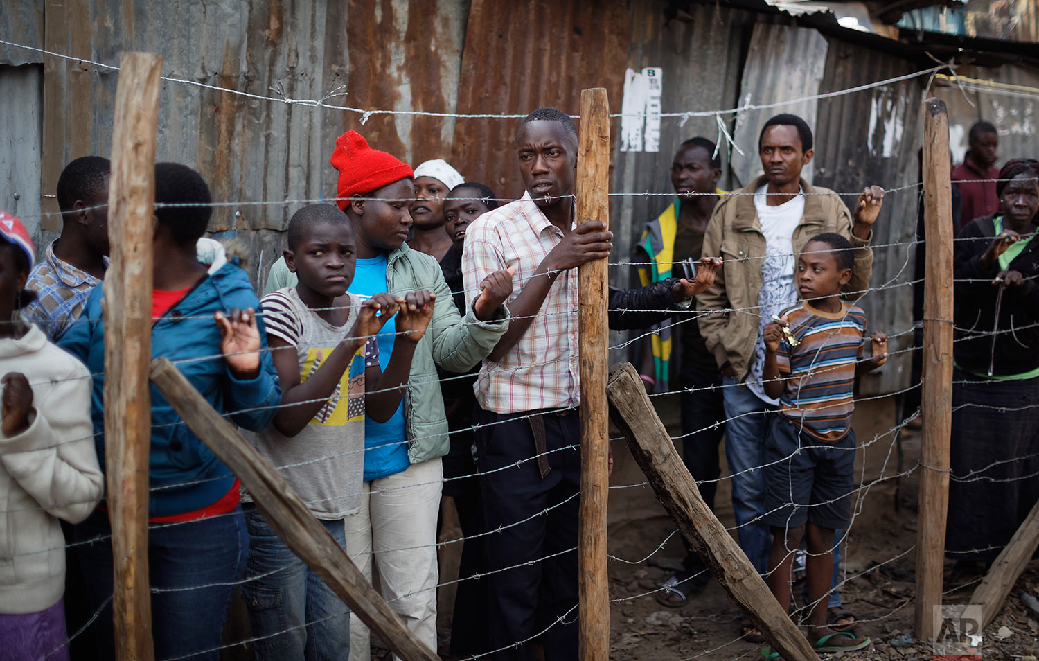 Residents look through a fence at the scene near the body of a man who had been shot in the head and who the crowd claimed had been shot by police, in the Mathare area of Nairobi, Kenya, Wednesday, Aug. 9, 2017. Kenya's election took an ominous turn on Wednesday as violent protests erupted in the capital. (AP Photo/Ben Curtis)