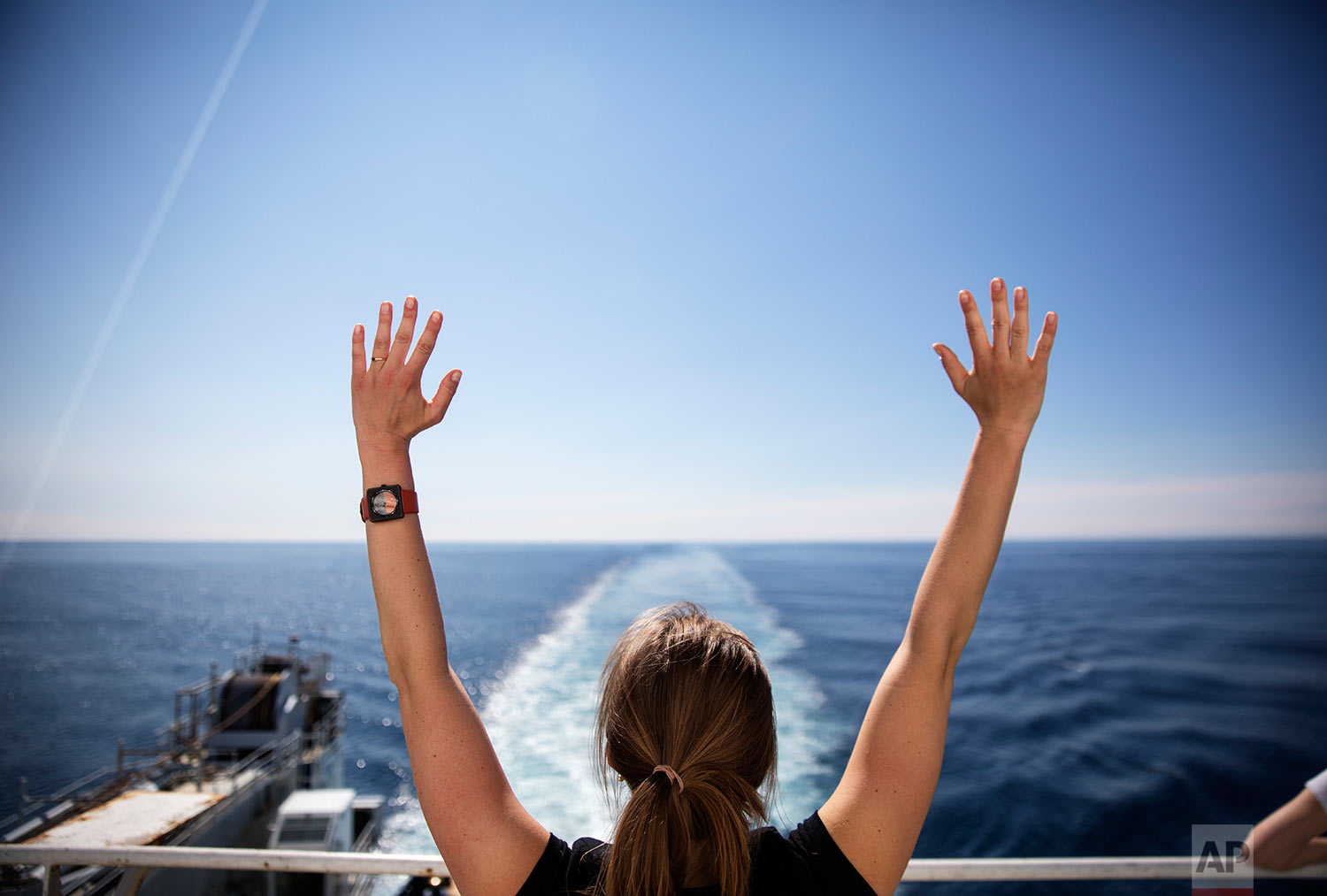 Daria Gritsenko stretches while doing yoga in the warm weather aboard the Finnish icebreaker MSV Nordica as it sails the Bering Sea to traverse the Northwest Passage through the Canadian Arctic Archipelago Thursday, July 13, 2017. As it made its way through the North Pacific, passing Chinese cargo ships, Alaskan fishing boats and the occasional far-off whale, members of the expedition soaked up the sun in anticipation of freezing weeks to come. (AP Photo/David Goldman)
