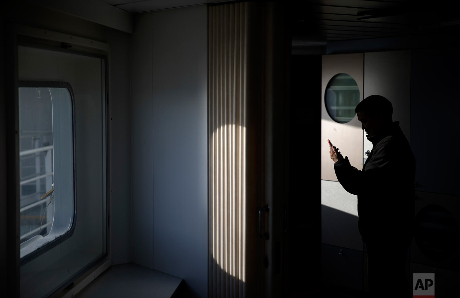 Trainee Maatiusi Manning tries to video chat with his family aboard the Finnish icebreaker MSV Nordica as it traverses the Northwest Passage through the Canadian Arctic Archipelago Wednesday, July 26, 2017. After two weeks at sea the ship's fragile internet connection went down for six days: no emails, no new satellite pictures to preview the route ahead. (AP Photo/David Goldman)