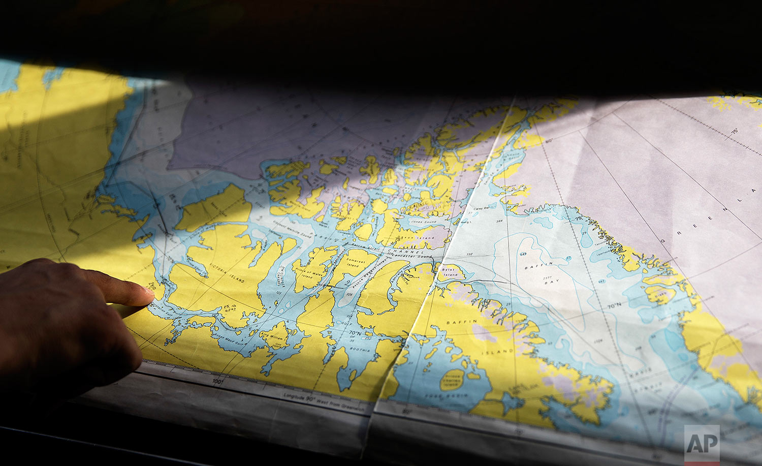 Trainee David Kullualik looks at a map of the Canadian Arctic Archipelago as the Finnish icebreaker MSV Nordica traverses the Northwest Passage, Monday, July 24, 2017. Researchers on the trip sought to observe the changes taking place in the region first hand, to gain a clearer picture of the effects of global warming already seen from space. Even the dates of the journey were a clue: The ship departed Vancouver in early July and arrived in Nuuk, Greenland on July 29th, the earliest transit ever of a region that isn't usually navigable until later in the year. (AP Photo/David Goldman)