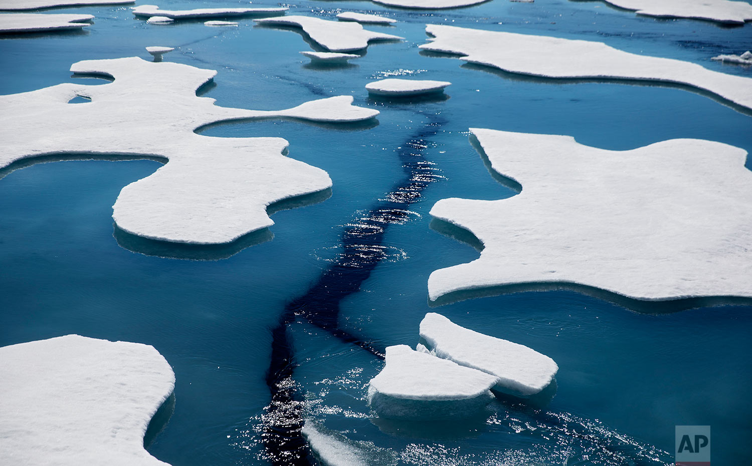 Sea ice breaks apart as the Finnish icebreaker MSV Nordica traverses the Northwest Passage through the Victoria Strait in the Canadian Arctic Archipelago Friday, July 21, 2017. Since the first orbital images were taken in 1979, Arctic sea ice coverage has dropped by an average of about 34,000 square miles each year _ almost the surface area of Maine or the country of Serbia. (AP Photo/David Goldman)