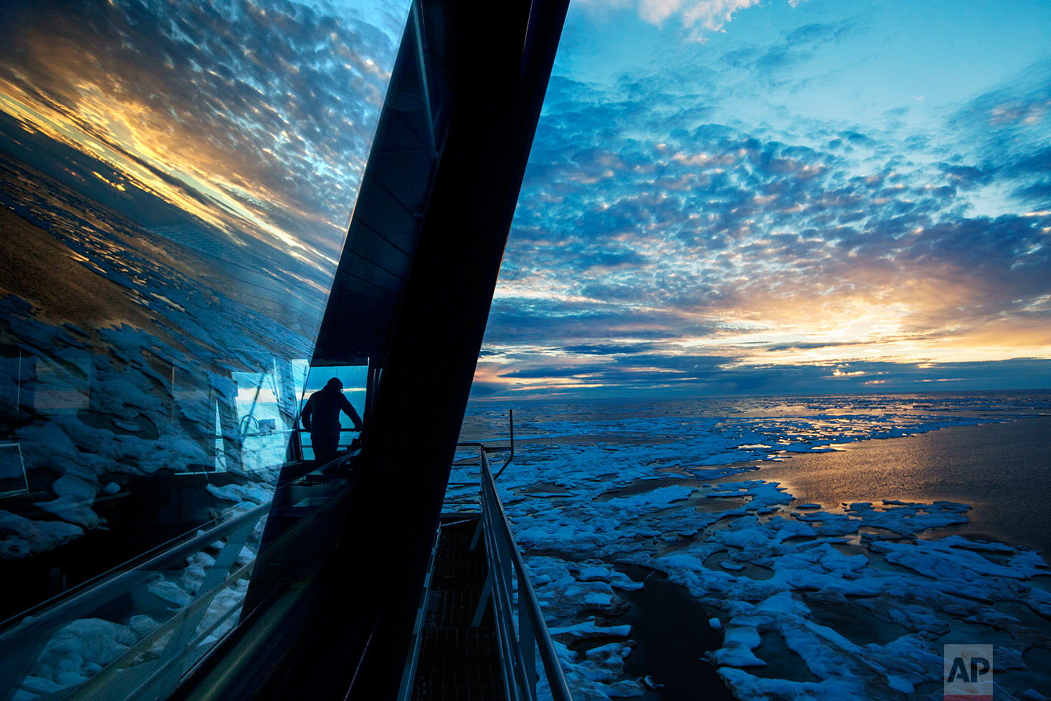 Nigel Greenwood, assistant ice navigator, looks out at the ice from the bridge while standing watch overnight aboard the Finnish icebreaker MSV Nordica as it traverses the Northwest Passage in the Canadian Arctic Archipelago, Friday, July 21, 2017. Modern mariners can get daily satellite snapshots of the ice and precise GPS locations that help them dodge dangerous shallows. But technology can be fickle. After two weeks at sea the ship's fragile internet connection went down for six days: no emails, no Google, no new satellite pictures to preview the route ahead. (AP Photo/David Goldman)