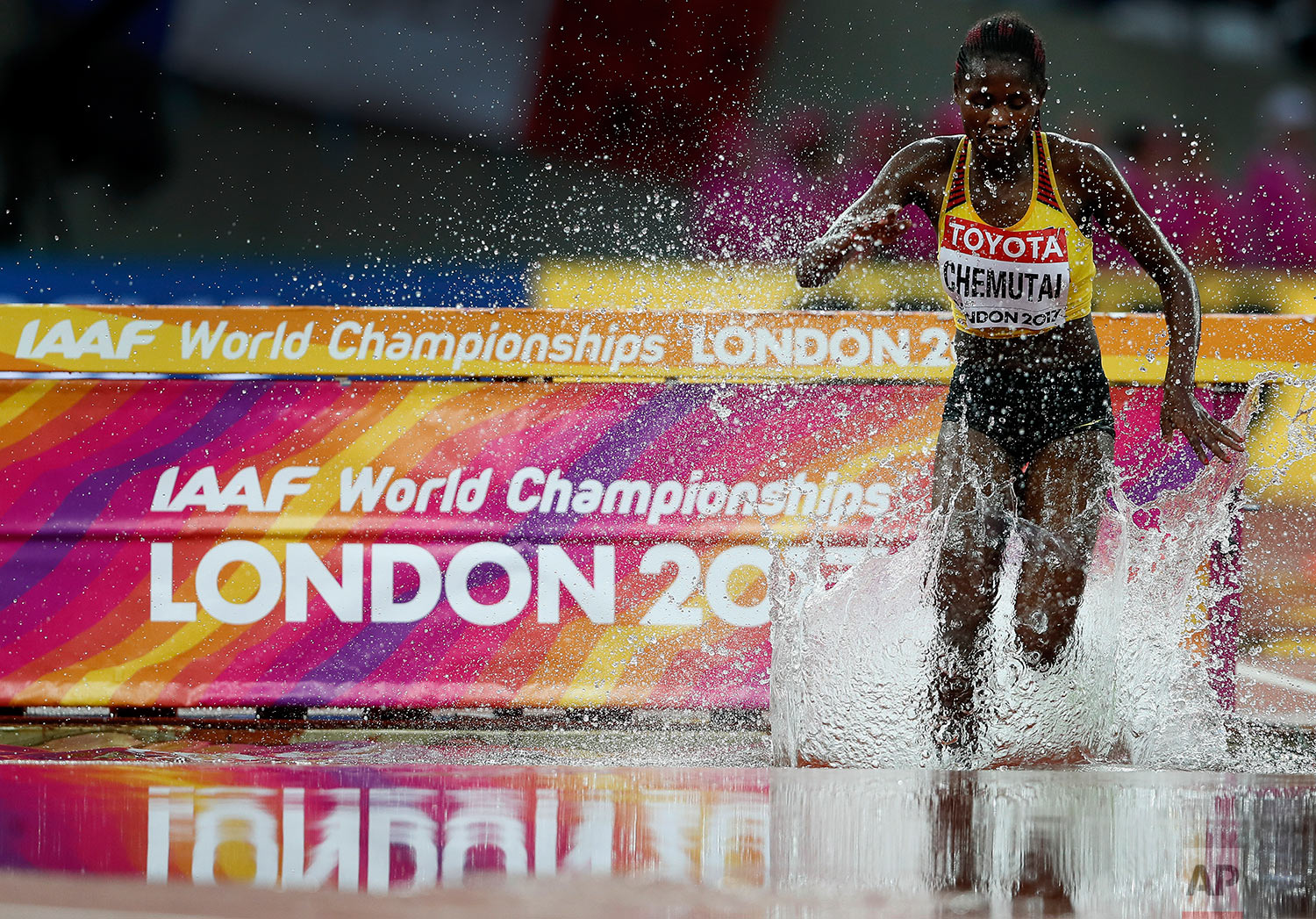 Uganda's Peruth Chemutai splashes into the water jump in a Women's 3000m Steeplechase heat during the World Athletics Championships in London Wednesday, Aug. 9, 2017. (AP Photo/Kirsty Wigglesworth)