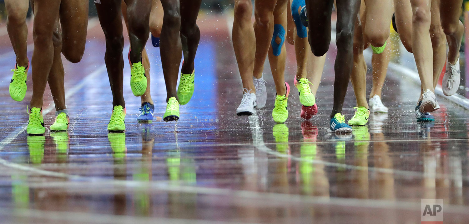 Competitors in the Women's 3000m Steeplechase are reflected on the wet track during the World Athletics Championships in London Wednesday, Aug. 9, 2017. (AP Photo/David J. Phillip)