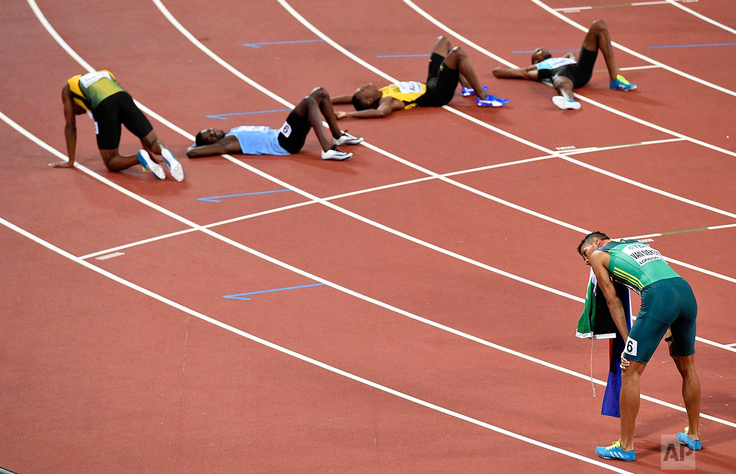 South Africa's Wayde Van Niekerk, right, rests after winning the Men's 400 meters final at the World Athletics Championships in London Tuesday, Aug. 8, 2017. (AP Photo/Martin Meissner)