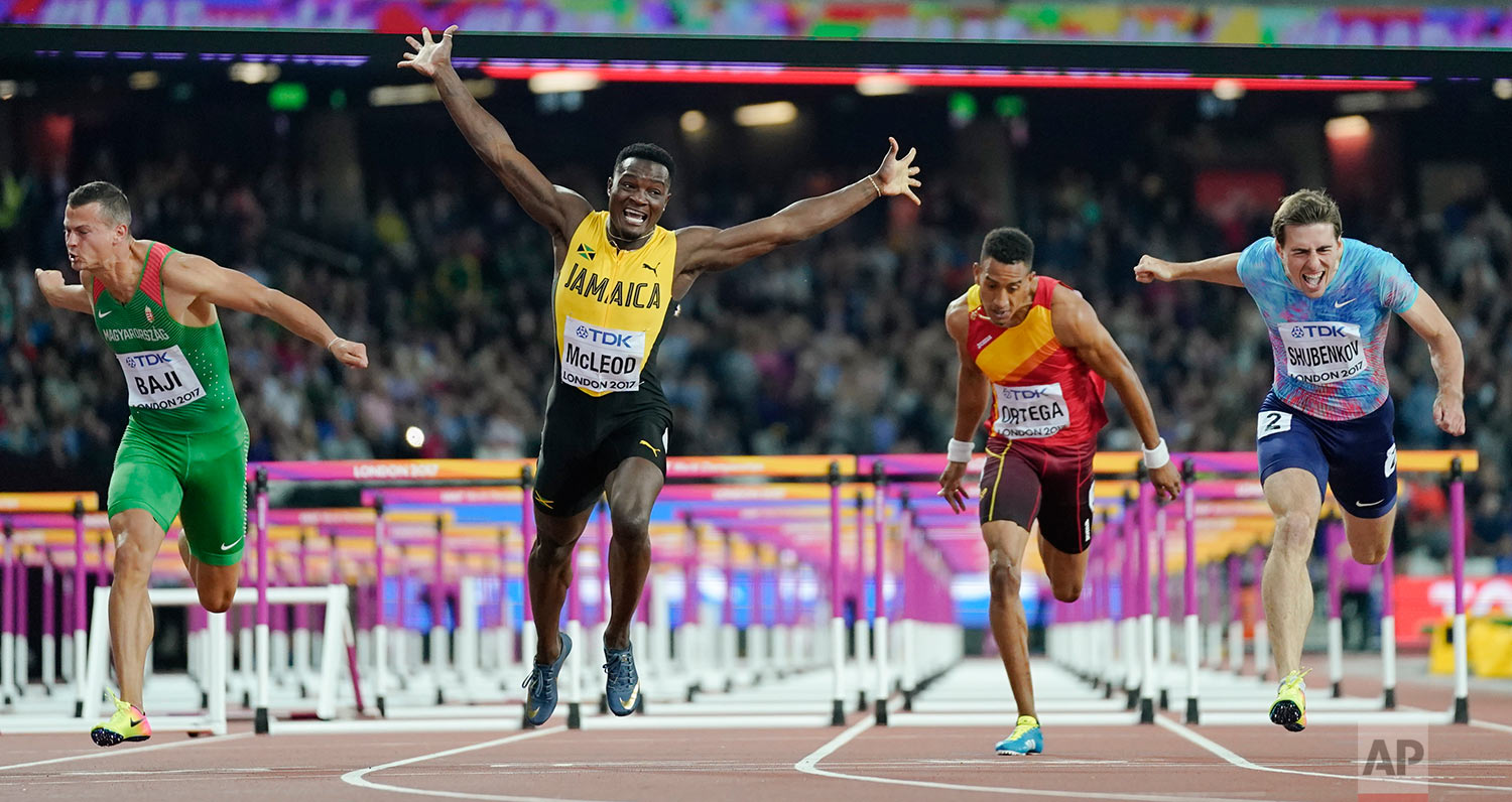 Jamaica's Omar Mcleod, second left, celebrates as he wins the gold medal in the final of the Men's 110m hurdles during the World Athletics Championships in London Monday, Aug. 7, 2017. At right Russia's Sergey Shubenkov, who took silver and at left Hungary's Balazs Baji who placed third. (AP Photo/David J. Phillip)