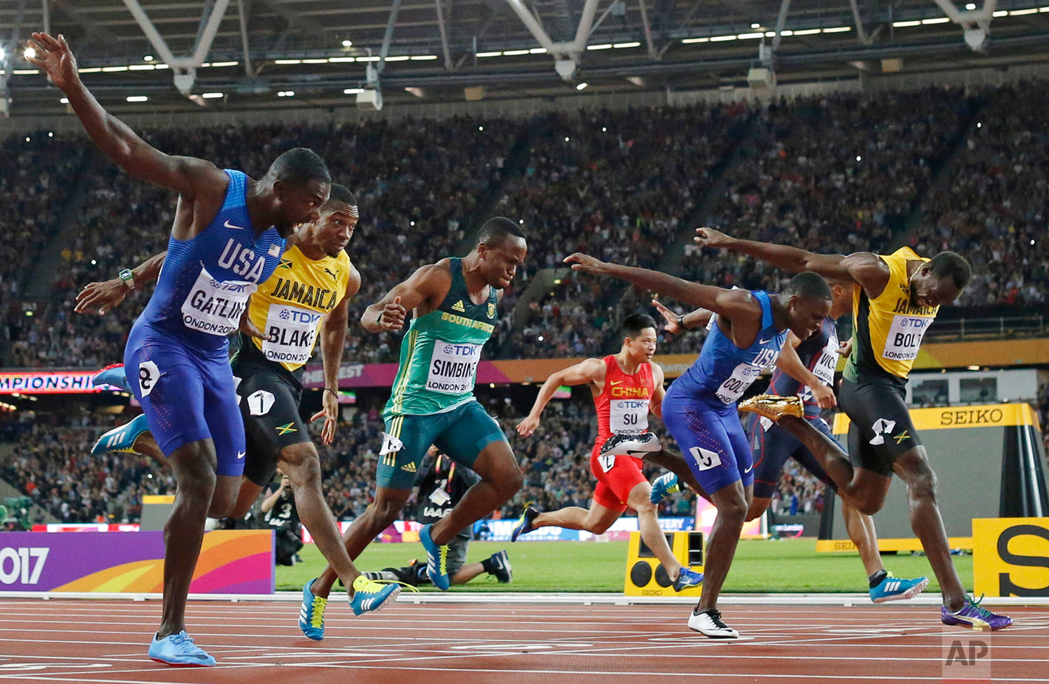 United States' Justin Gatlin, left, crosses the line to win gold ahead of silver medal winner United States' Christian Coleman, second right, and bronze medal winner Jamaica's Usain Bolt, right, in the men's 100m final during the World Athletics Championships in London Saturday, Aug. 5, 2017. (AP Photo/Matt Dunham)