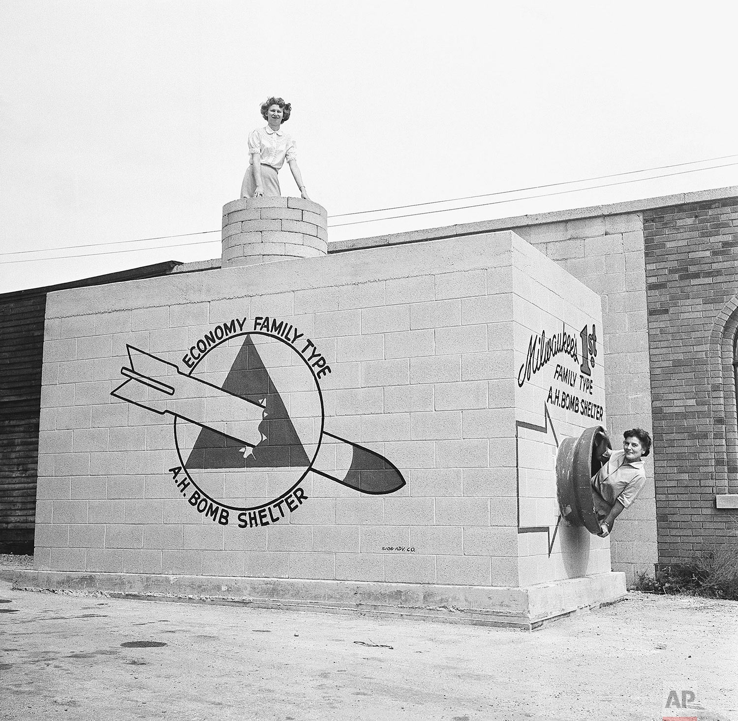 In this Sept. 12, 1958 photo, Beverly Wysocki, top, and Marie Graskamp, right, emerge from a new family-type bomb shelter on display in Milwaukee, Wis. (AP Photo)
