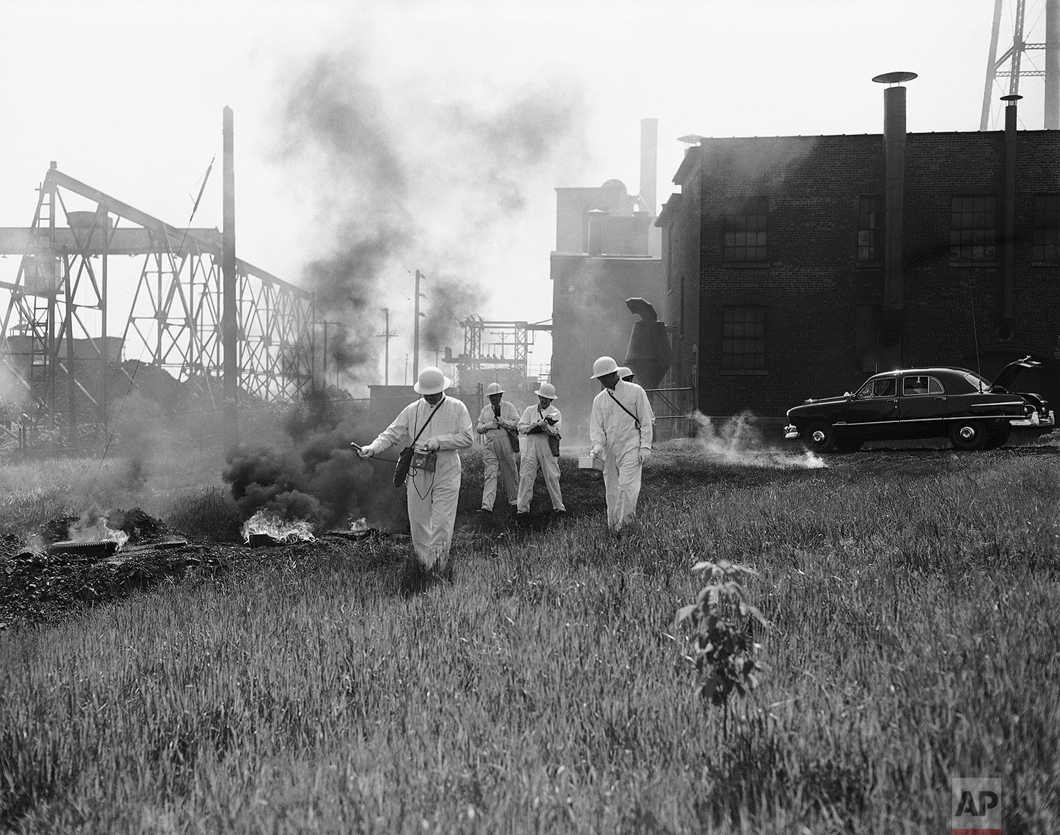 """In this May 26, 1951 photo, a radiological team checks a """"bombed"""" area for radiation after a simulated atomic bombing in Utica, N.Y. (AP Photo/Arthur Z. Brooks)"""