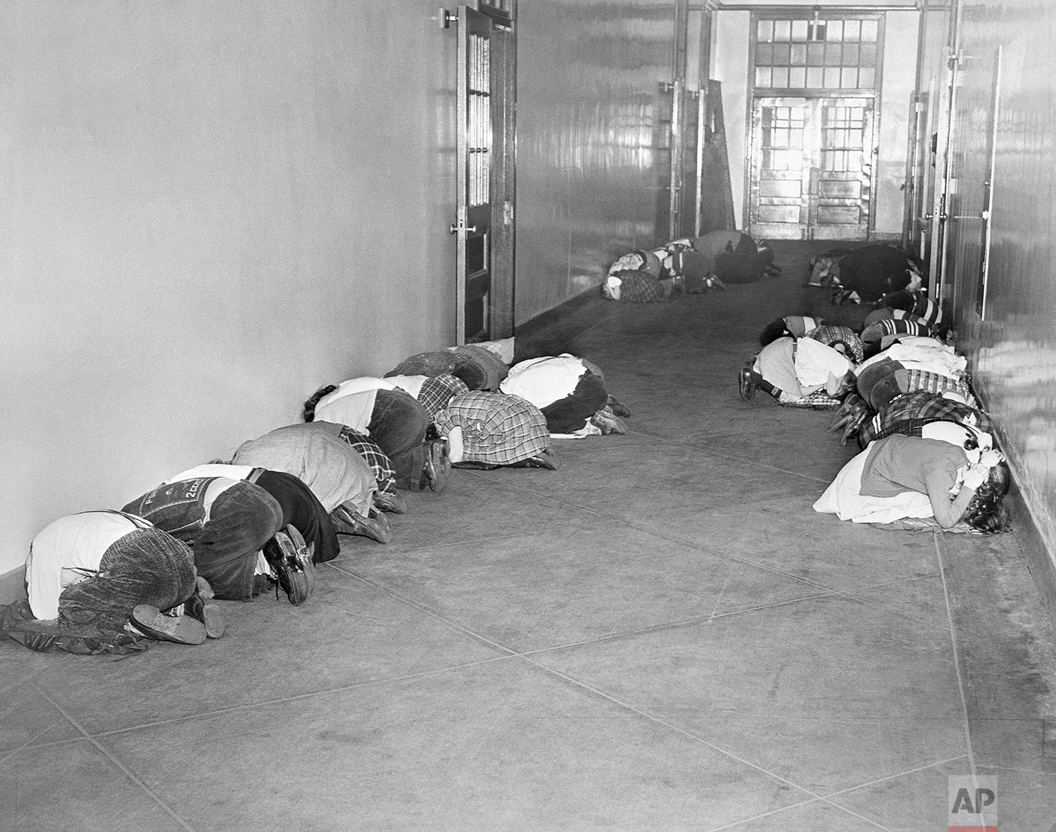 In this Jan. 25, 1951 file photo, students at Thomas Jefferson elementary school kneel in the hallway during an air raid drill being practiced by public schools in Baltimore. (AP Photo)