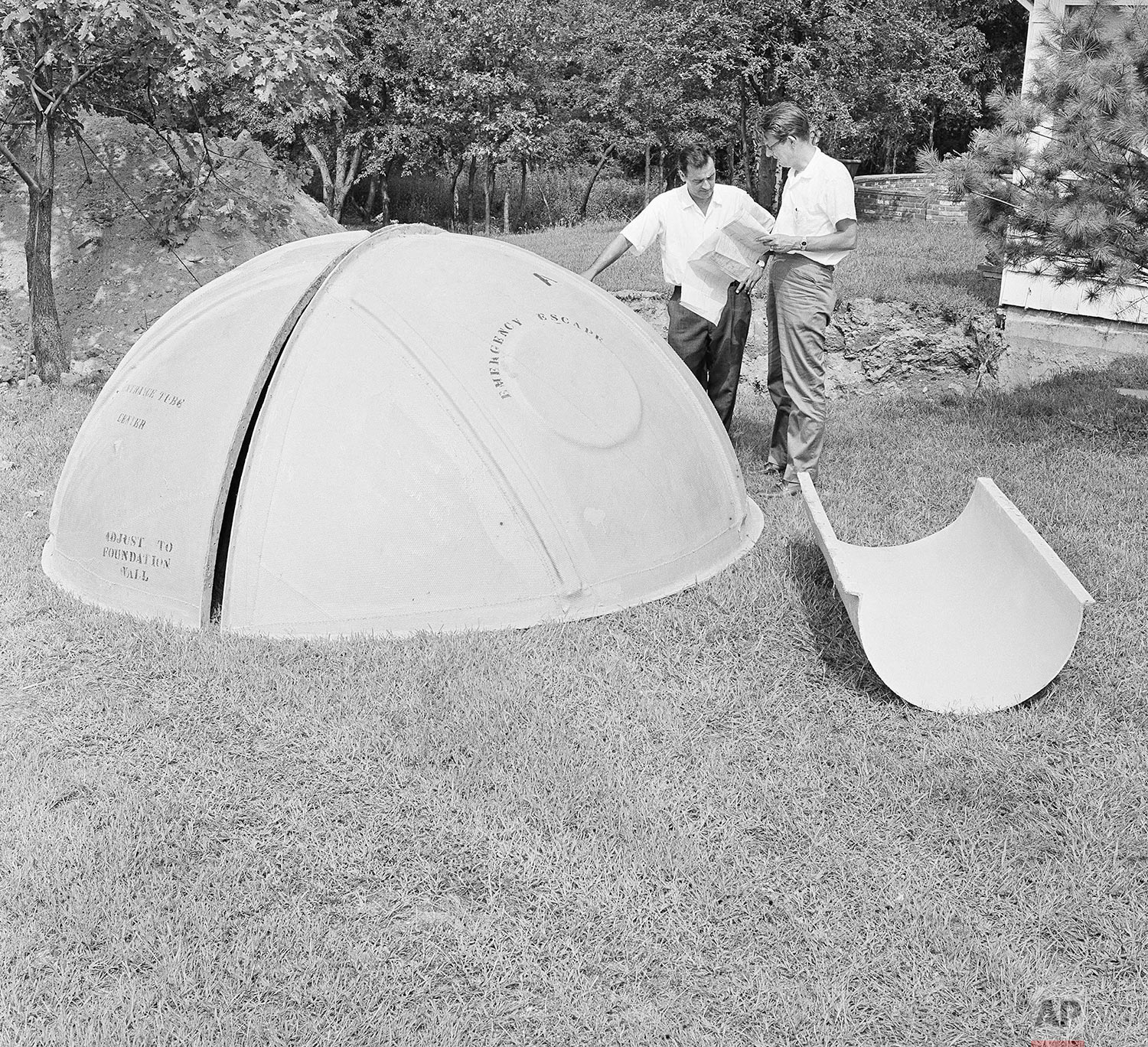 In this Sept. 7, 1961 photo, bomb shelter manufacturer engineers Vincent Carubia, left, and Eward Klein study specifications for a fiber glass dome shelter being installed on an estate in Locust Valley, N.Y. (AP Photo)
