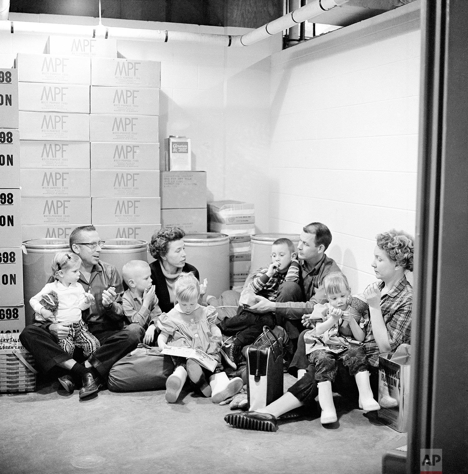 In this Jan. 29, 1962 photo, the Spalding family, left, and the Richmond family demonstrate how people of the town would sit out a nuclear attack and its radioactive aftermath in Los Alamos, N.M., birthplace of the atomic and hydrogen bombs. (AP Photo)