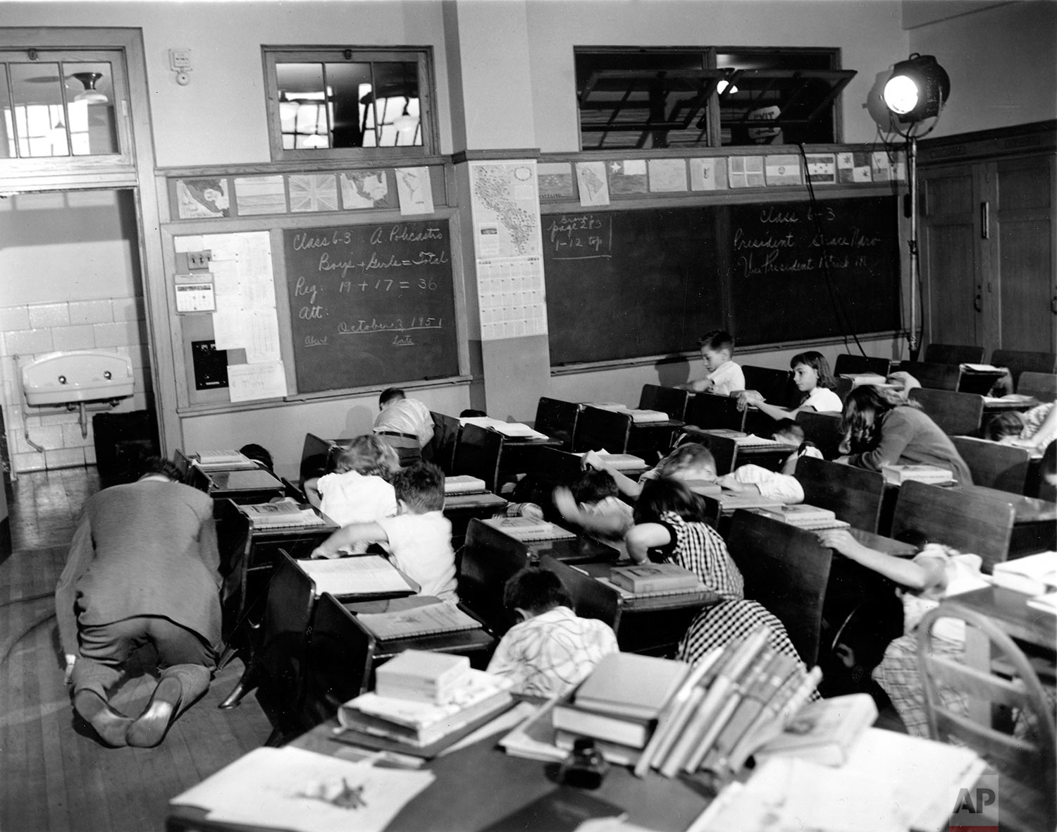 """In this Nov. 21, 1951 picture, sixth grade students crouch under or beside their desks along with their teacher, Vincent M. Bohan, left, as they act out a scene from the Federal Civil Defense administration film """"Duck and Cover"""" at Public School 152 in the Queens borough of New York City. Even before the March 11 earthquake and resulting tsunami that led to the Japanese nuclear crisis, Americans were bombarded with contradictory images and messages that frighten even when they try to reassure. It started with the awesome and deadly mushroom cloud rising from the atomic bomb, which led to fallout shelters and school duck-and-cover drills. (AP Photo/Dan Grossi)"""