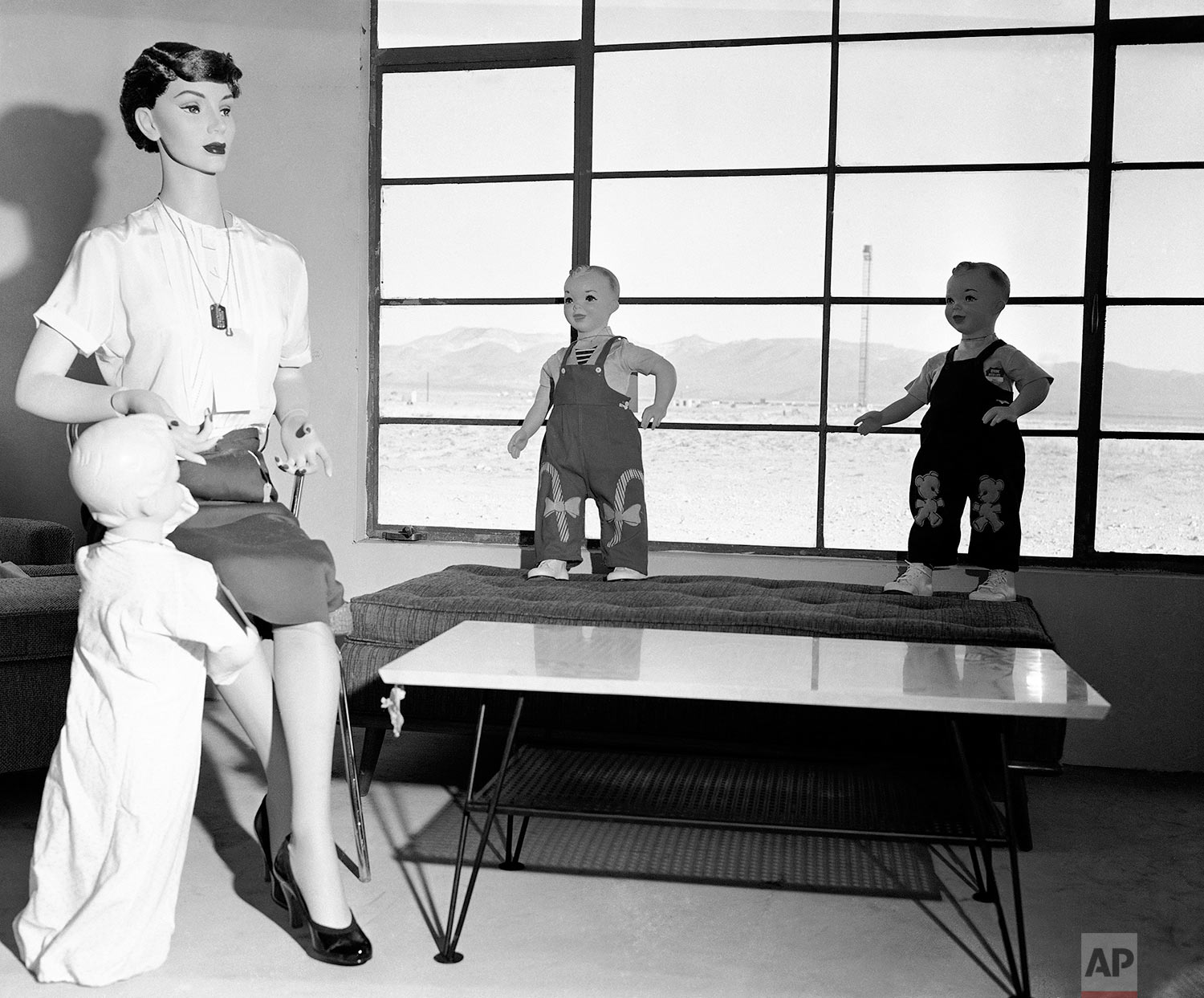 Mannequins that represent a typical American family, will soon experience the fury of an atomic blast with the power of 40,000 tons of TNT, at Yucca Flats, Nev., April, 24, 1955. The test is being conducted to determine the survival chances of an atomic attack. Through the picture window is the tower 4700 feet away on which the detonation will occur. (AP Photo/Dick Strobel)
