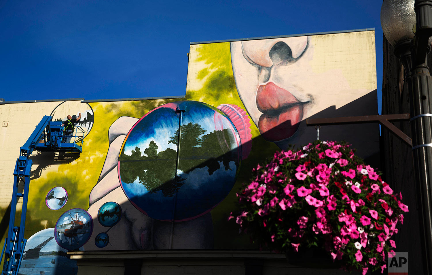 Artist Douglas Orr paints a mural on a building in Aberdeen, Wash., Friday, June 16, 2017. Orr has been painting a block-long mural of a little girl blowing bubbles, each circle the scene of an imagined, hopeful future. Nearby hangs one of the baskets of pink petunias that decorate light posts all over town, watered regularly by residents trying to make their city feel alive again. (AP Photo/David Goldman)