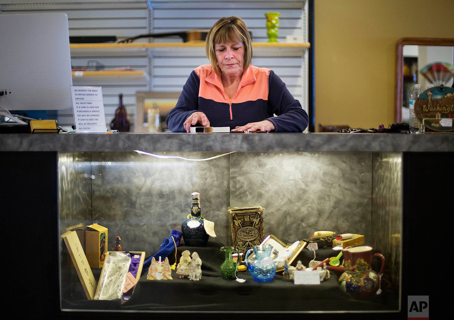 """Stacie Blodgett, who voted for Donald Trump, works in her antique and pawn shop in Aberdeen, Wash., Tuesday, June 13, 2017. """"Has he done anything good yet?"""" she asks. """"Has he?"""" She hopes Trump understands the stakes in places like this, with little room left for error from Washington, D.C. There, he is tweeting insults about senators and CNN. Here, her neighbors have been reduced to living in cars. (AP Photo/David Goldman)"""