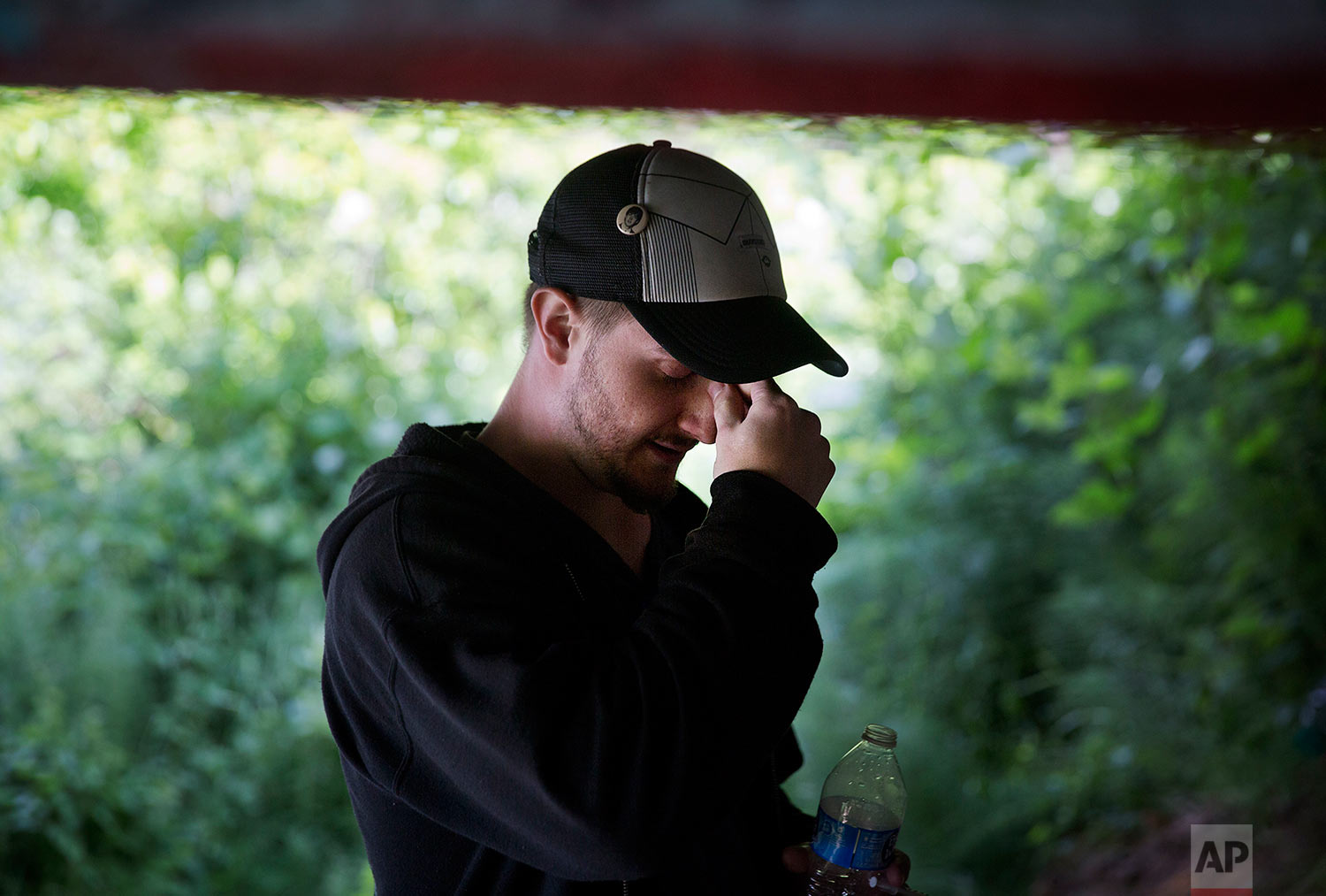 """Forrest Wood, 24, pauses after injecting heroin into this arm under a bridge along the Wishkah River at Kurt Cobain Memorial Park in Aberdeen, Wash., Tuesday, June 13, 2017. He's tried to quit; the drug only delays the sickness and shame that set in when he doesn't shoot up. """"I'm trying to get myself to feel like I have some sort of purpose,"""" he said. """"I just want to be happy, that's all."""" (AP Photo/David Goldman)"""