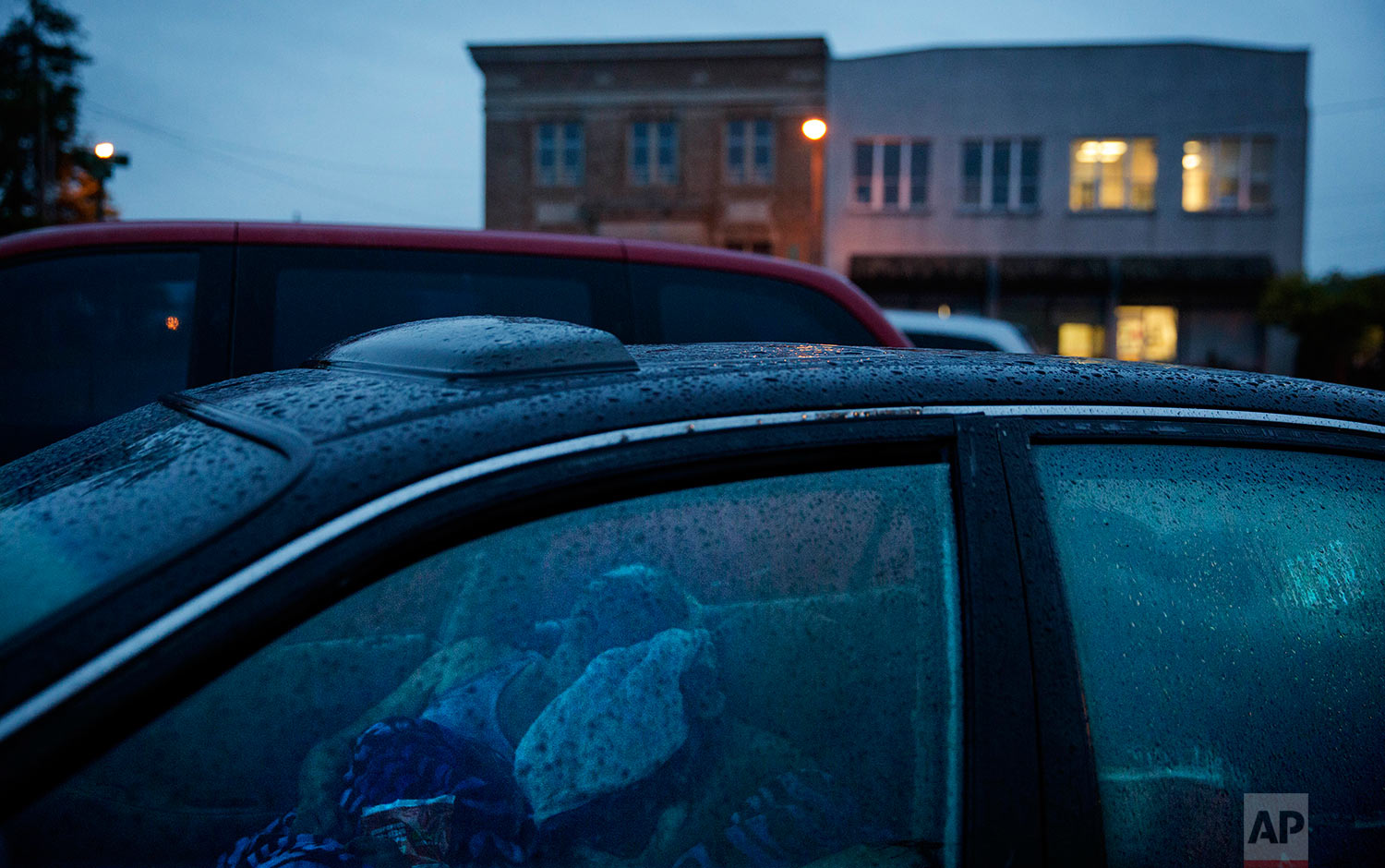 """Staci Hadley, left, and boyfriend Deric Hensler, hidden, sleep in their car overnight in a parking lot outside the methadone clinic before it opens where they get treated for their drug addiction in Hoquiam, Wash., Thursday June 15, 2017. """"Not too long ago we were thinking 'oh how the mighty have fallen',"""" said Hadley. The two used to have jobs, bank accounts, credit cards, a house before Hensler lost his job and insurance to cover methadone treatments. """"I know we're kind of messed out right now,"""" added Hadley. """"But this is not my life."""" (AP Photo/David Goldman)"""