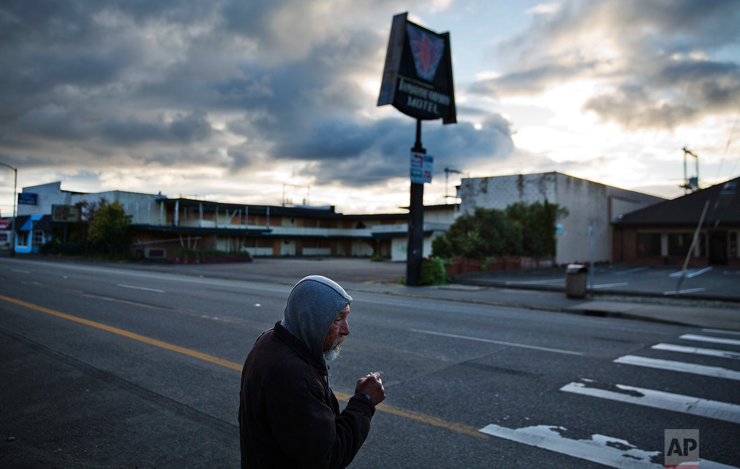 A man walks in front of a dilapidated motel in a rundown section of Aberdeen, Wash., Tuesday, June 13, 2017. The county's population is shrinking, growing sicker, growing poorer as many young and able move away. Just 15 percent of those left behind have college degrees. A quarter of children grow up poor. There is a critical shortage of doctors because it's hard to practice medicine in poor, rural places. (AP Photo/David Goldman)