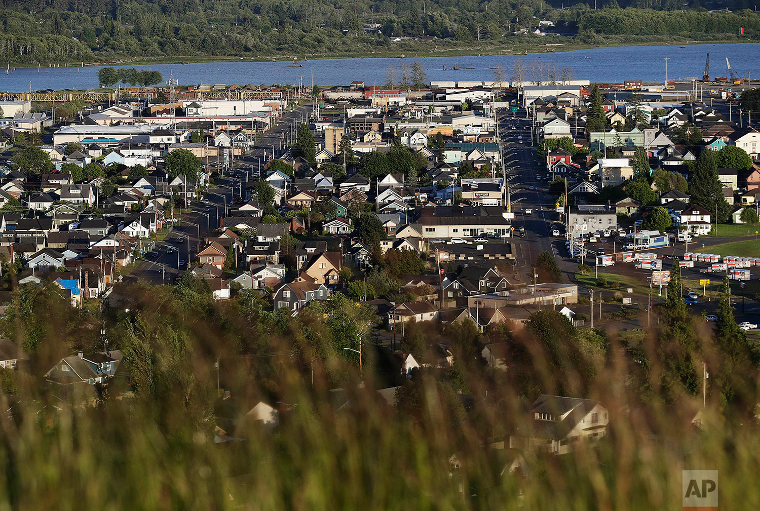 Aberdeen, Wash., is seen along the Chehalis River Friday, June 16, 2017. Aberdeen was built as a boom town at the turn of the 20th century. Its spectacular landscape, the Chehalis River carves through tree-topped hills to the harbor, offered ships easy access to the Pacific Ocean. Millionaire lumber barons built mansions on the hills. There were restaurants and theaters and traffic that backed up as the drawbridge leading into town seesawed up and down for ship after ship packed with logs and lumber. Now that drawbridge pretty much stays put. (AP Photo/David Goldman)