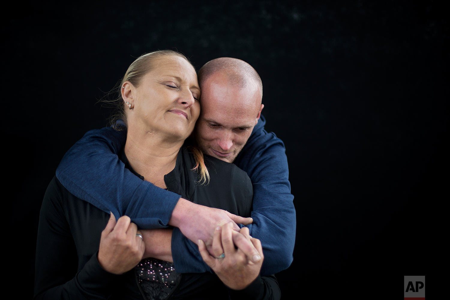 """Staci Hadley, left, and boyfriend Deric Hensler, embrace during a portrait while stopping by a needle exchange program in Aberdeen, Wash., Wednesday June 14, 2017. """"It's crazy how things can spiral out of control. Not too long ago, a year ago, we had credit cards and bank accounts, jobs, a house,"""" said Hadley. (AP Photo/David Goldman)"""