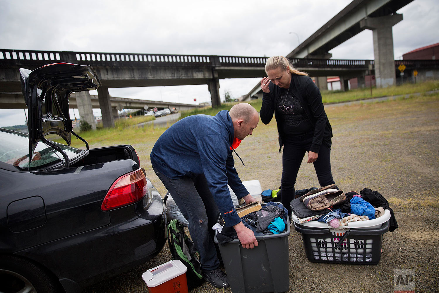 Staci Hadley, right, and boyfriend Deric Hensler rearrange their personal items out of their car which they are living out of in Aberdeen, Wash., Wednesday June 14, 2017. The couple had gotten clean on a methadone program, moved into a nice apartment and started building a better life. Then Hensler lost his job, his insurance and couldn't get methadone anymore. Now they're back on drugs and living in their car and they're trying to figure out a safe place to park and sleep for the night. (AP Photo/David Goldman)