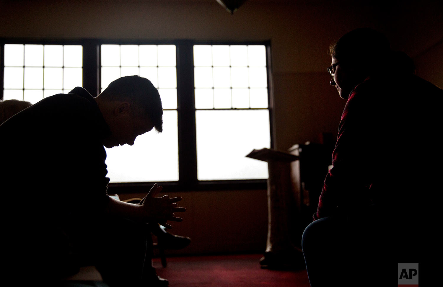 """Aaron Scott, left, prays during a service conducted by Rev. Sarah Monroe, right, at Chaplains on the Harbor church in Westport, Wash., Thursday, June 15, 2017. """"I don't think our politicians know how high the stakes are here, and after so many years have gone by with our situation still as devastated as it is, I don't know if they care,"""" Monroe says. """"I'm not sure how much worse it can get, and at the same time I'm afraid to see how much worse it can get."""" (AP Photo/David Goldman)"""