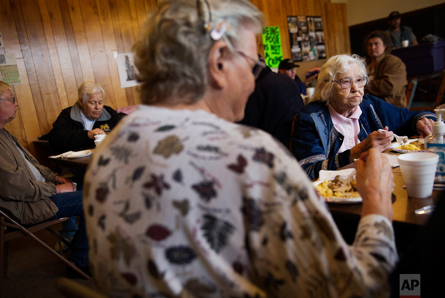 Verna MacDonald, 87, right, who is on Medicare, sits for a free meal put on for the community at Chaplains on the Harbor church in Westport, Wash., Thursday, June 15, 2017. The county's population is shrinking, growing sicker, growing poorer as many young and able move away. Just 15 percent of those left behind have college degrees. A quarter of children grow up poor. There is a critical shortage of doctors because it's hard to practice medicine in poor, rural places. (AP Photo/David Goldman)