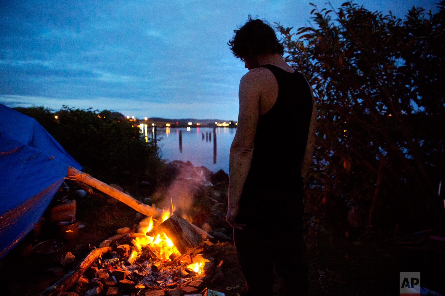"""Alan, who is getting treated at a nearby methadone clinic while trying to kick his heroin addiction, stands by the fire outside his tent at the homeless encampment where he lives along the river in Aberdeen, Wash., Wednesday June 14, 2017. """"I'm just trying to make it,"""" said Alan who asked not to have his last name published and dreams of having his own RV some day. (AP Photo/David Goldman)"""