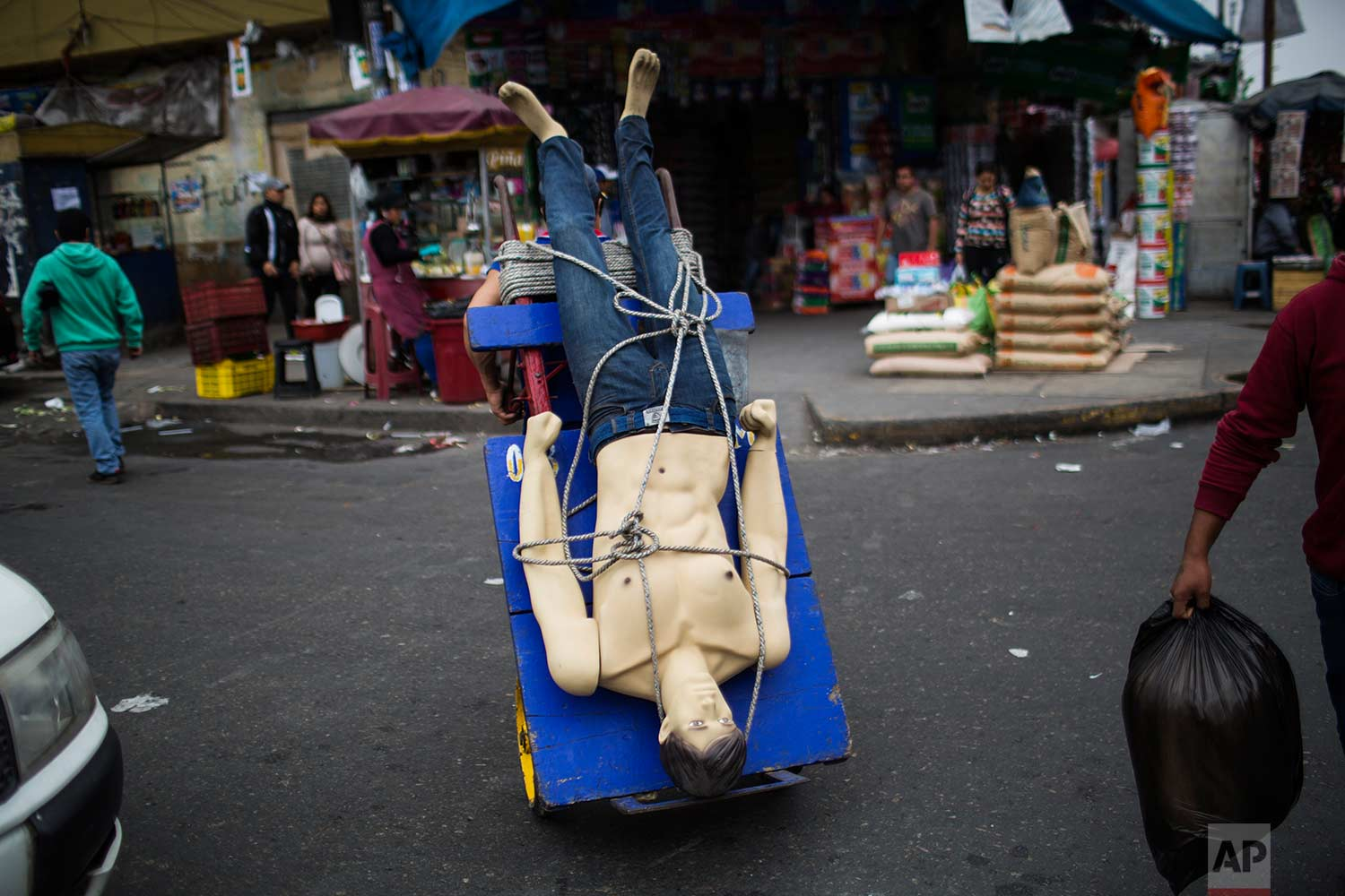 "A loader or ""cargador"" carries a mannequin on his dolly at the Gamarra market, one of Latin America's largest and busiest textile markets, in Lima, Peru, Monday, Aug. 14, 2017. (AP Photo/Rodrigo Abd)"