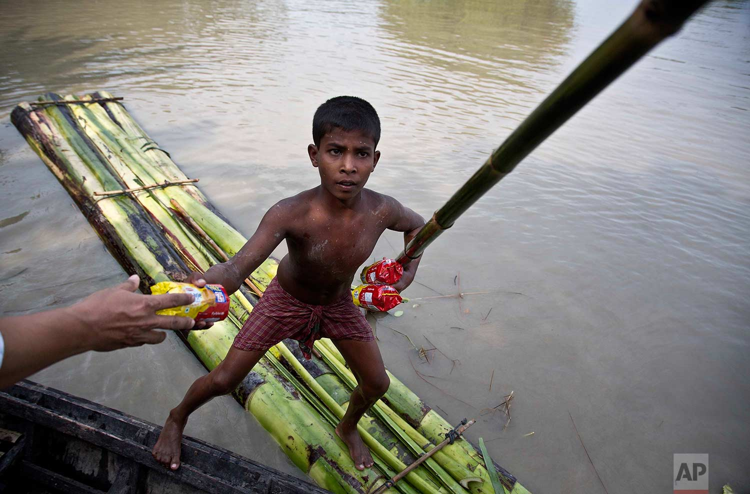A flood affected boy on a makeshift banana raft collects biscuit packets distributed by a government official from a boat in Pokoria village, east of Gauhati, north eastern Assam state, India, Monday, Aug. 14, 2017. (AP Photo/Anupam Nath)