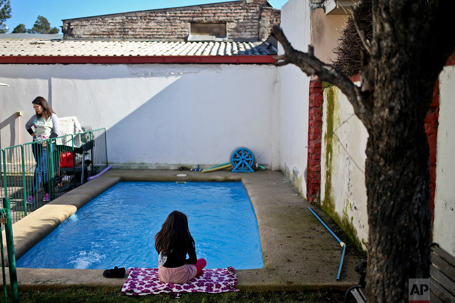 In this July 18, 2017 photo, transgender girl Luna sits beside the pool at her home in Santiago, Chile. An uncomfortable incident two years ago about Luna's gender led her parents to file a lawsuit demanding her name and gender be legally changed from boy to girl on her birth certificate. (AP Photo/Esteban Felix)