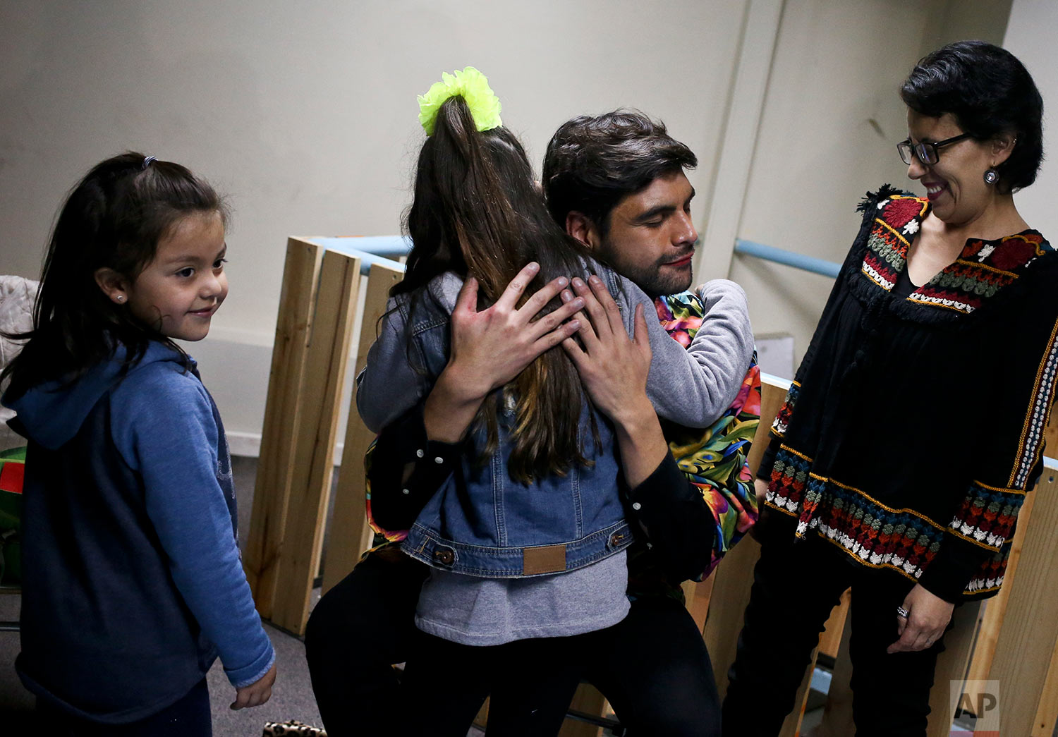 In this July 8, 2017 photo, transgender girl Selenna embraces a storyteller at the end of his reading as her transgender friend Mathilda stands by, at a bookshop in Santiago, Chile. The story teller, who is also a drag queen, told stories that touched on the themes of inclusion and identity diversity. (AP Photo/Esteban Felix)