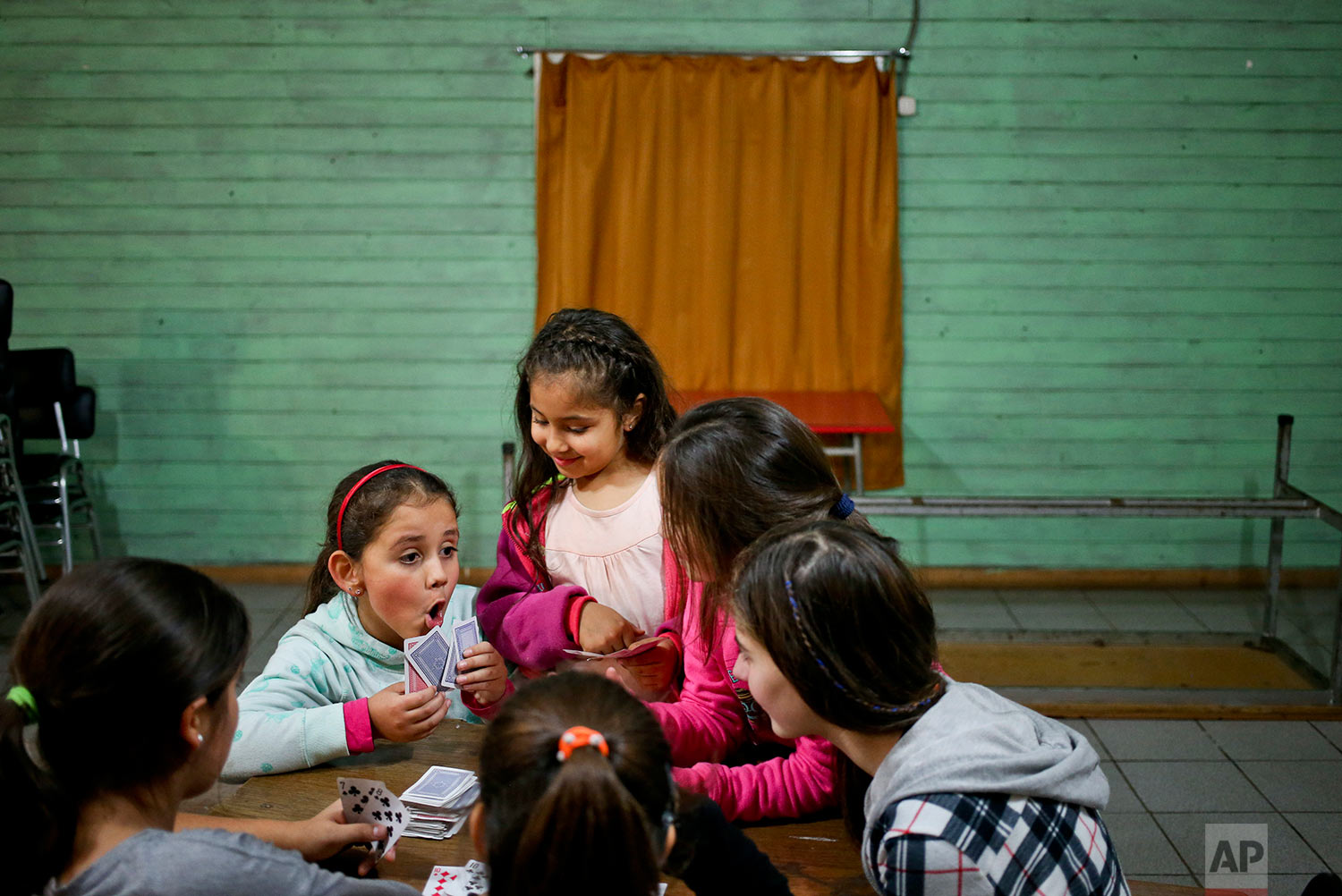 In this June 30, 2017 photo, transgender girl Selenna, left, plays cards during a break with other girls during a dance class at her community center in Santiago, Chile. Selenna's mother, Evelyn Silva, said she struggled to find a school that would accept a girl whose birth certificate still lists her as a boy, though she finally succeeded. (AP Photo/Esteban Felix)