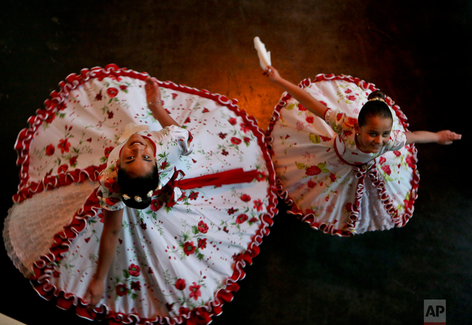In this Aug. 19, 2017 photo, transgender girls Josefa, 13, left, and Selenna, 8, pose for a picture as they twirl in traditional Chilean dance costumes before an event marking Transgender Children Day in Santiago, Chile. The center-left government has been pushing an array of measures for gender rights, ranging from decriminalizing some abortions to demanding greater acceptance for transgender people in general and children in particular. (AP Photo/Esteban Felix)