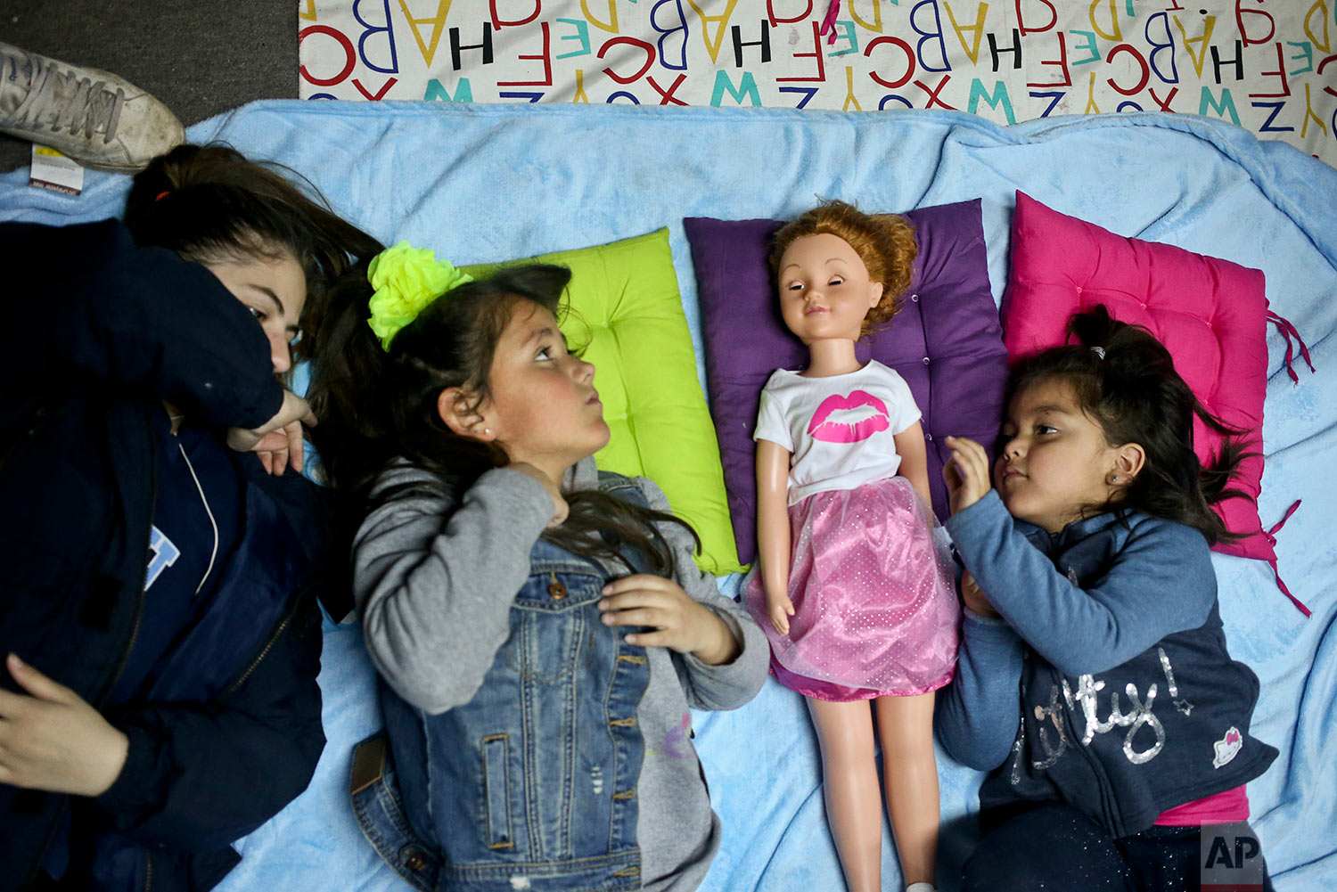 """In this July 8, 2017 photo, transgender girls Selenna, second from left, and Mathilda, right, play with a doll as their mothers attend a meeting on gender identity at a bookshop in Santiago, Chile. Selenna said she never liked celebrating her birthday because she would always get toy cars. """"Maybe they didn't notice it,"""" said Selenna. """"But I was always (a girl)."""" (AP Photo/Esteban Felix)"""