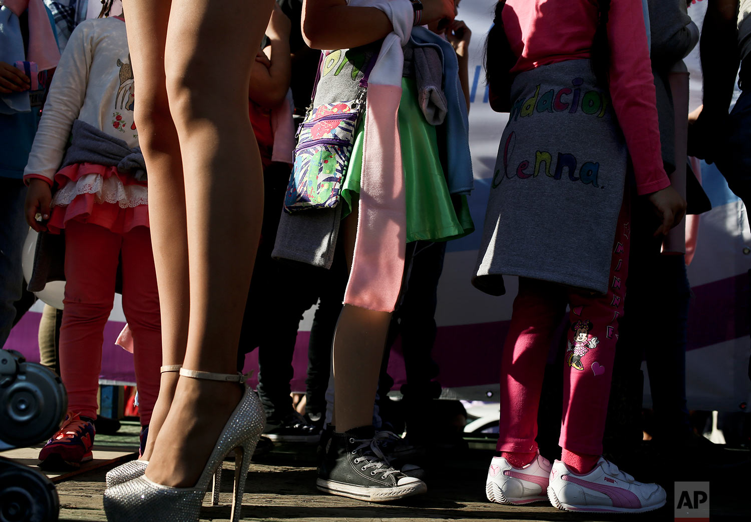 In this July 1, 2017 photo, transgender girls stand by a transvestite during a Gay Pride march in Santiago, Chile. The center-left government has been pushing an array of measures for gender rights, ranging from decriminalizing some abortions to demanding greater acceptance for transgender people in general and children in particular. (AP Photo/Esteban Felix)