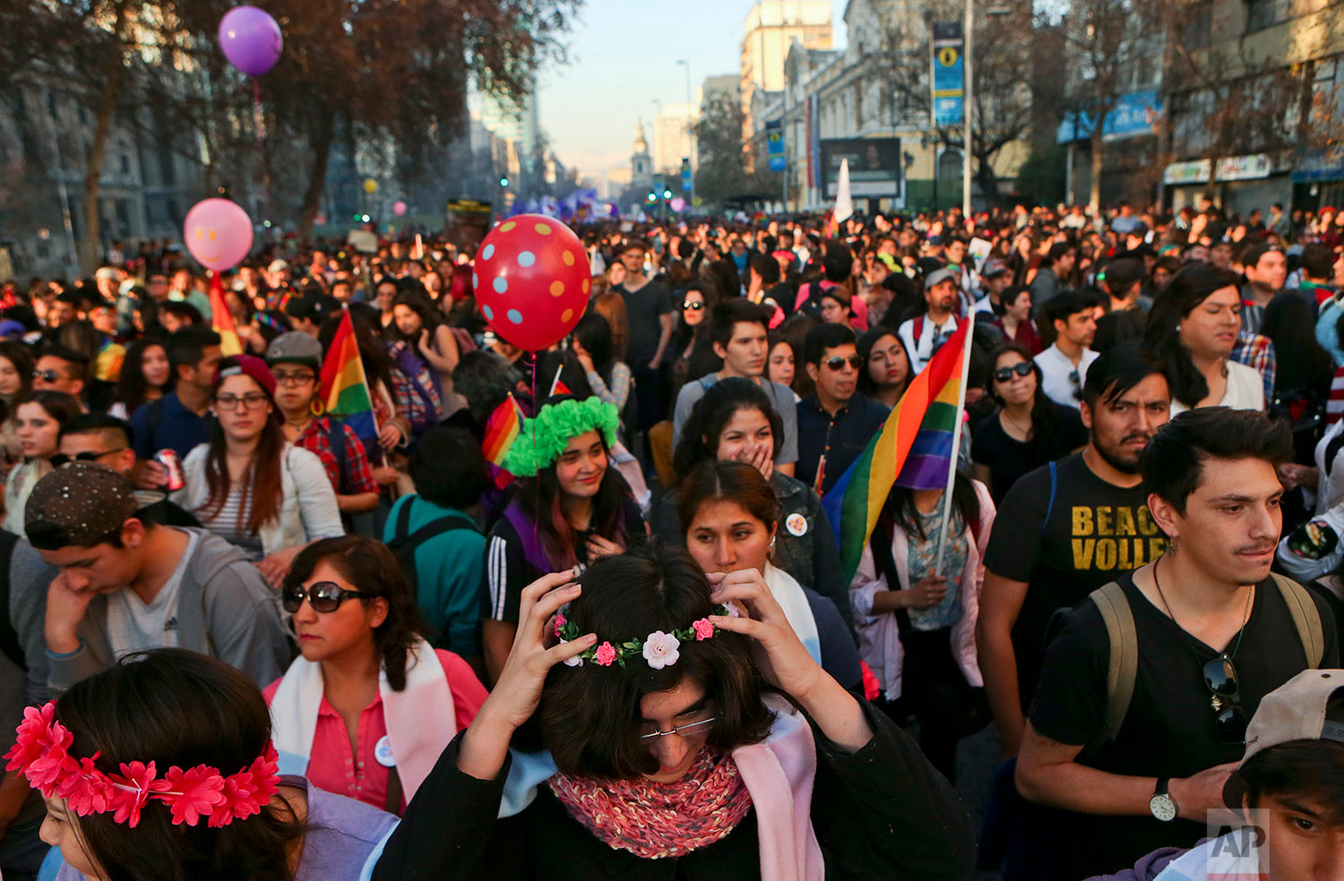 In this July 1, 2017 photo, Angela, below center, places a crown of flowers on her head as she attends a Gay Pride march alongside other transgender children in Santiago, Chile. The transgender children at the parade had socially transitioned to their chosen gender with the backing of their families. (AP Photo/Esteban Felix)