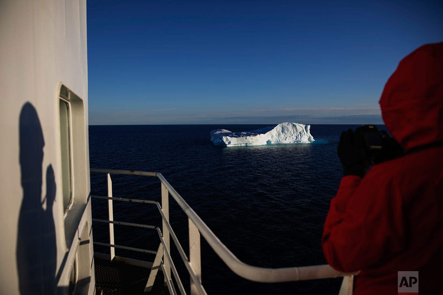 Researcher Tiina Jaaskelainen takes a picture of an iceberg floating in Baffin Bay in the Canadian Arctic Archipelago while aboard the Finnish icebreaker MSV Nordica, Tuesday, July 25, 2017.  (AP Photo/David Goldman)